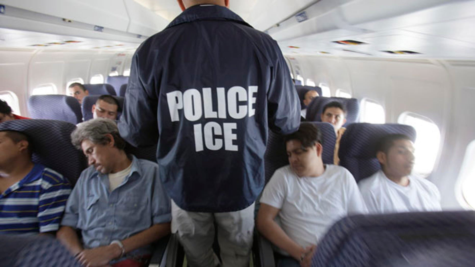 File photo--An Immigration and Customs Enforcement agent walks down the aisle among  shackled Mexican immigrants a boarded a U.S. Immigration and Customs Enforcement charter jet for deportation. May 25, 2010.  (AP Photo/LM Otero)