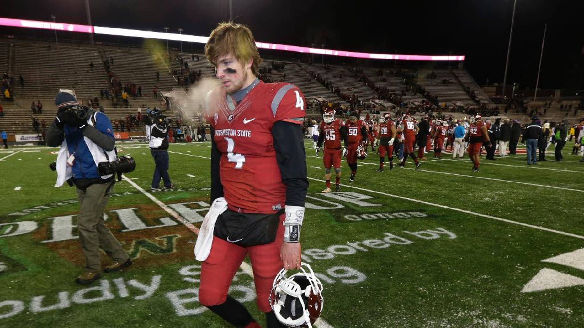 Washington State quarterback Luke Falk walks off the field, Saturday, Nov. 29, 2014, in Pullman, Wash., after Washington defeated Washington State 31-13 in an NCAA college football game. (AP Photo/Ted S. Warren)