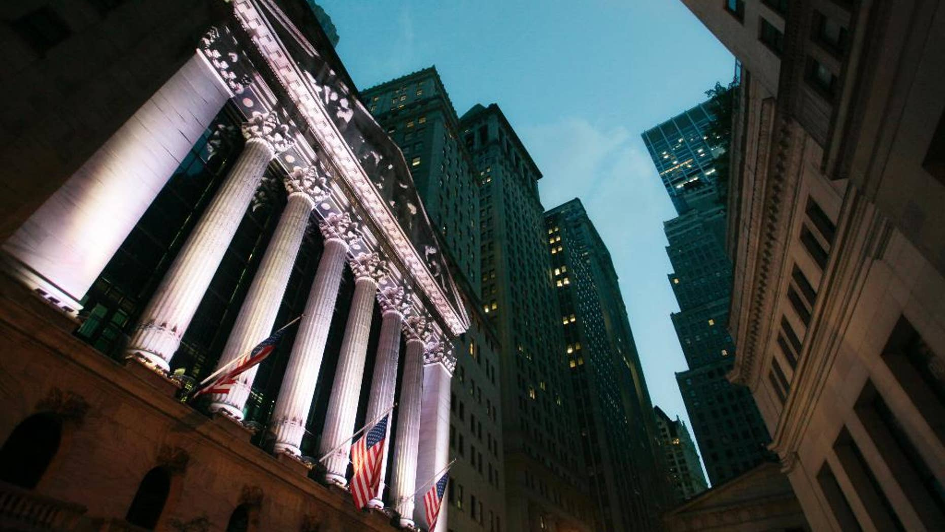 FILE - In this Oct. 8, 2014 file photo, American flags fly in front of the New York Stock Exchange, in New York. Stocks are little changed in early trading Monday, Nov. 3, 2014, as investors brace for a busy week of news. (AP Photo/Mark Lennihan, File)