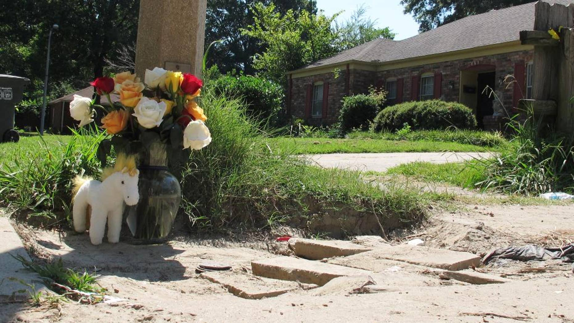 A makeshift memorial rests on the sidewalk Monday, Aug. 3, 2015, at the location where Memphis, Tenn., Police Officer Sean Bolton was fatally shot. Tremaine Wilbourn, the ex-con accused of killing the Memphis Police Officer turned himself into federal authorities Monday, after a two-day manhunt. (AP Photo/Adrian Sainz)