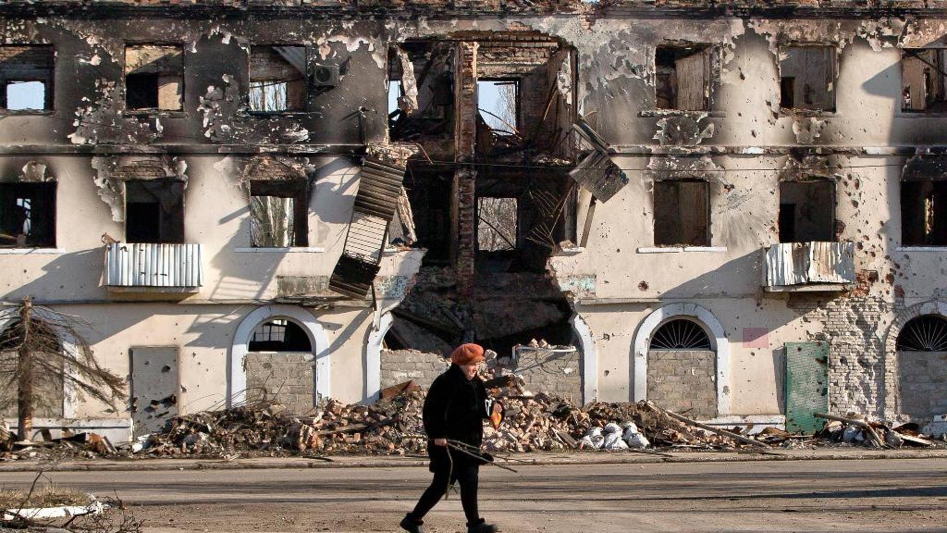 March 9, 2015: An elderly woman walks by a destroyed building in Vuhlehirsk, Ukraine.