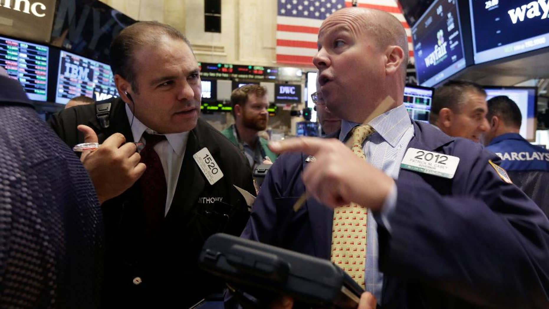 Traders Anthony Riccio, left, and Patrick Casey work on the floor of the New York Stock Exchange, Thursday, Oct. 2, 2014. U.S. markets were mostly flat in early trading Thursday, follow a sell-off the day before, as U.S. investors had little reaction to comments from European Central Bank President Mario Draghi, who announced new economic stimulus measures for the continent. (AP Photo/Richard Drew)