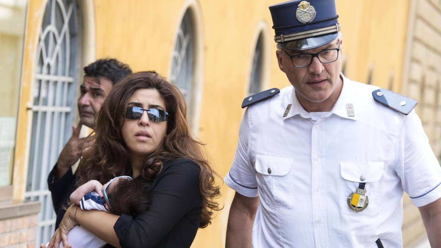 Public relations expert Francesca Chaouqui walks next a Vatican Gendarme as she arrives at the Vatican for her trial.