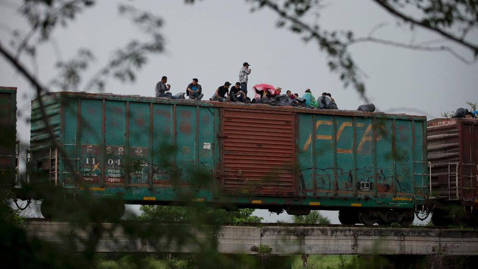 FILE - In this June 20, 2014 file photo, Central American migrants wait atop the freight train they had been traveling north on, as it starts to rain after the train suffered a minor derailment outside Reforma de Pineda, Chiapas state, Mexico. Mexico now deports more Central American migrants than the United States, a dramatic shift since the U.S. asked Mexico for help a year ago with a spike in illegal migration, especially among unaccompanied minors. (AP Photo/Rebecca Blackwell, File)