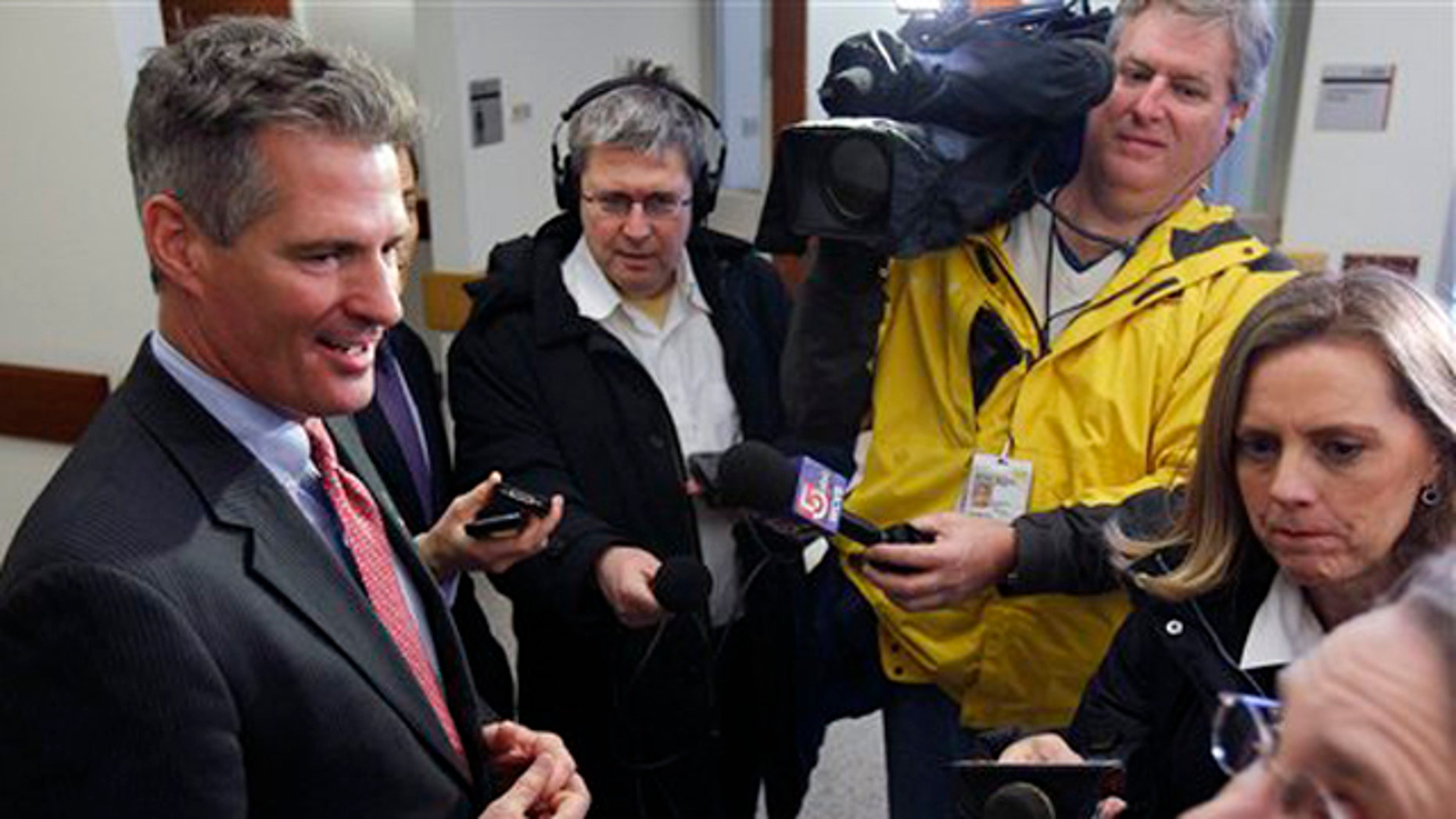 FILE: Then-Sen. Scott Brown talks with members of the media during a tour of Boston Police headquarters in Boston.