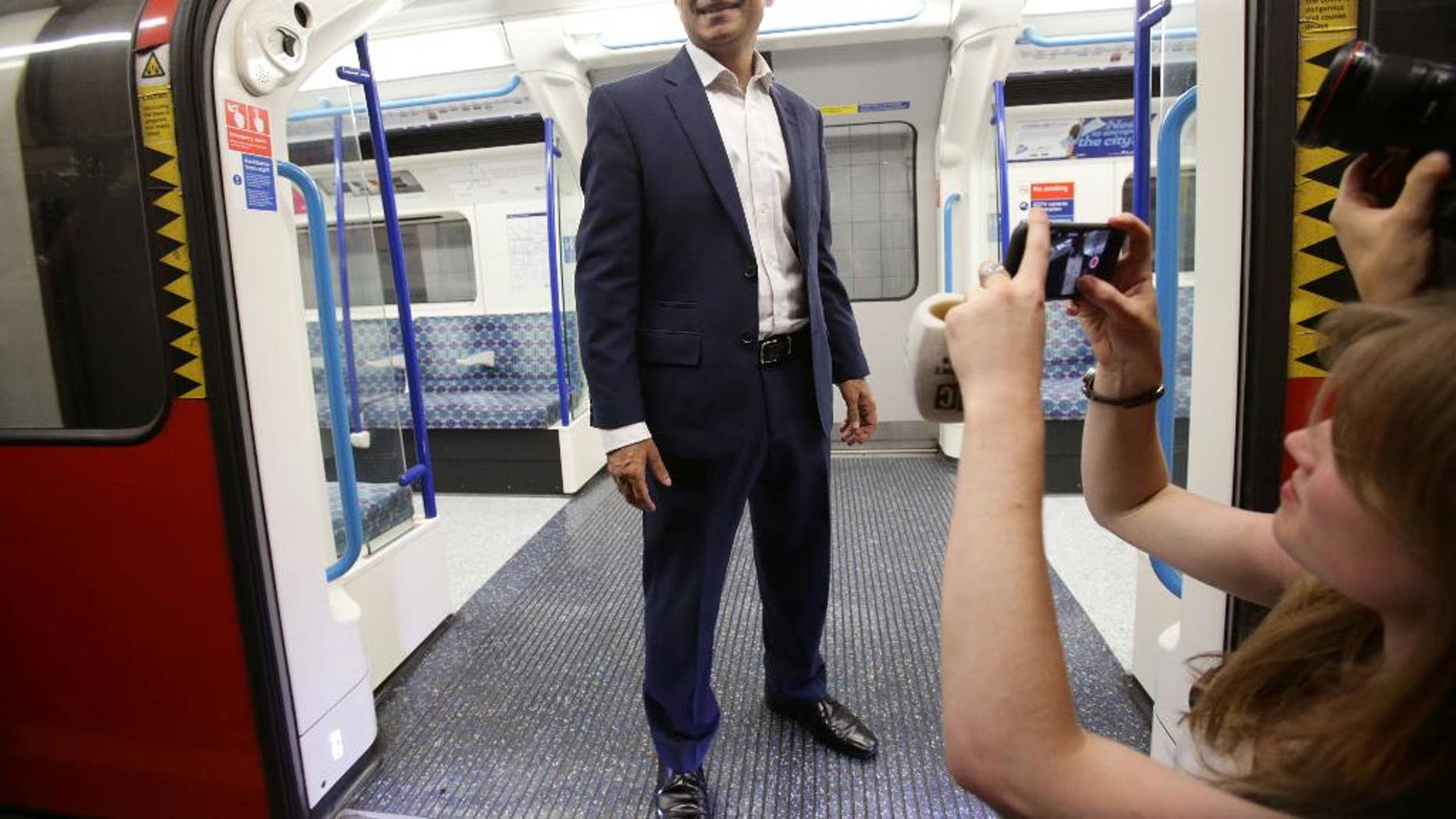 Mayor of London Sadiq Khan poses for the media on a Victoria line tube train carriage at Brixton Underground station in London during the launch of London's Night Tube Saturday, Aug. 20, 2016. The London Underground introduced limited overnight service Saturday, a move city leaders hope will make the British capital a truly 24-hour city and bolster the local economy. (Yui Mok/PA via AP)