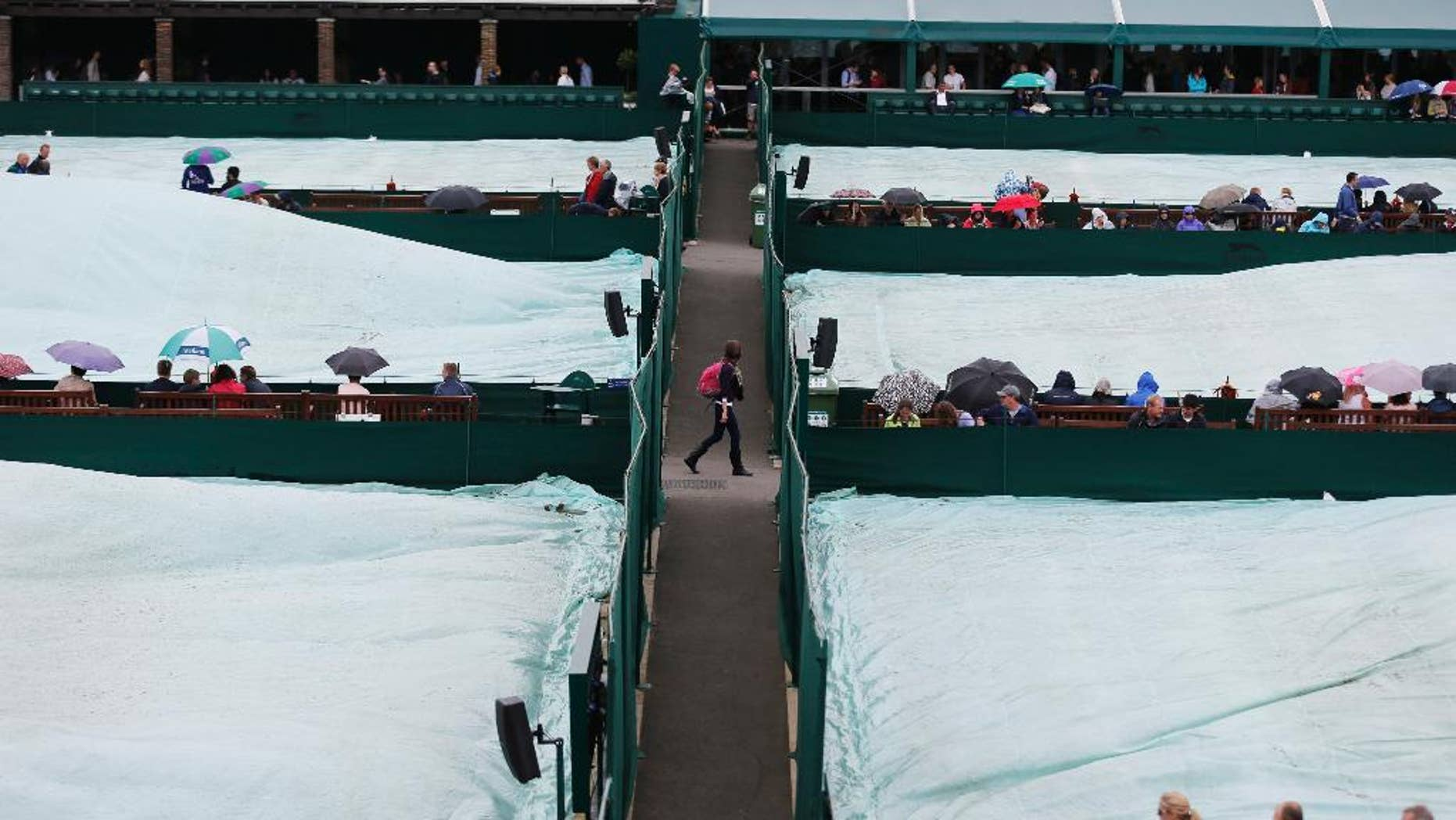 Courts are covered as rain delays the start of matches at the All England Lawn Tennis Championships in Wimbledon, London, Friday, June 27, 2014. (AP Photo/Ben Curtis)