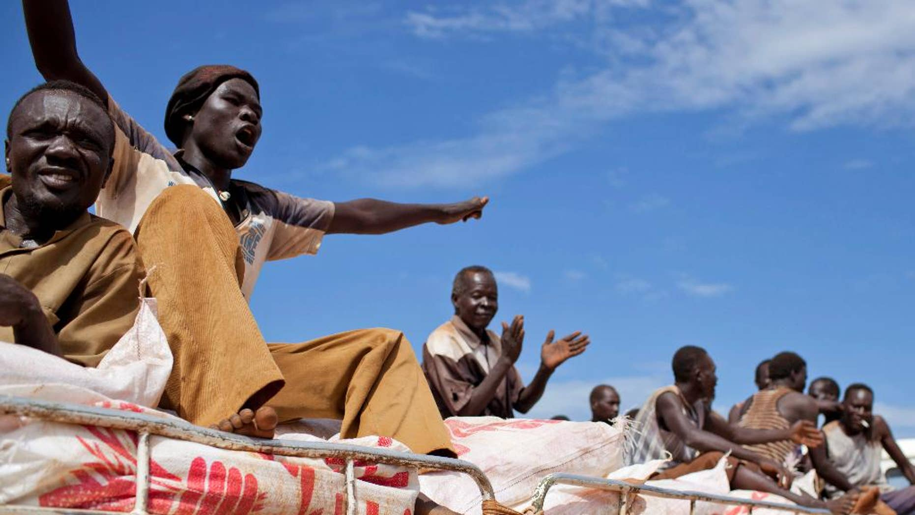 """FILE - In this Sunday Sept. 16, 2012 file photo, South Sudanese men sing and clap as they ride on the truck carrying WFP food supplies to a warehouse, in Yida camp, South Sudan.  The World Food Program said Friday April 14, 2017 it is """"horrified"""" to learn that three of its South Sudan workers were killed this week in violence in the western town of Wau, as the country's civil war continues under warnings of possible genocide. (AP Photo/Mackenzie Knowles-Coursin, File)"""