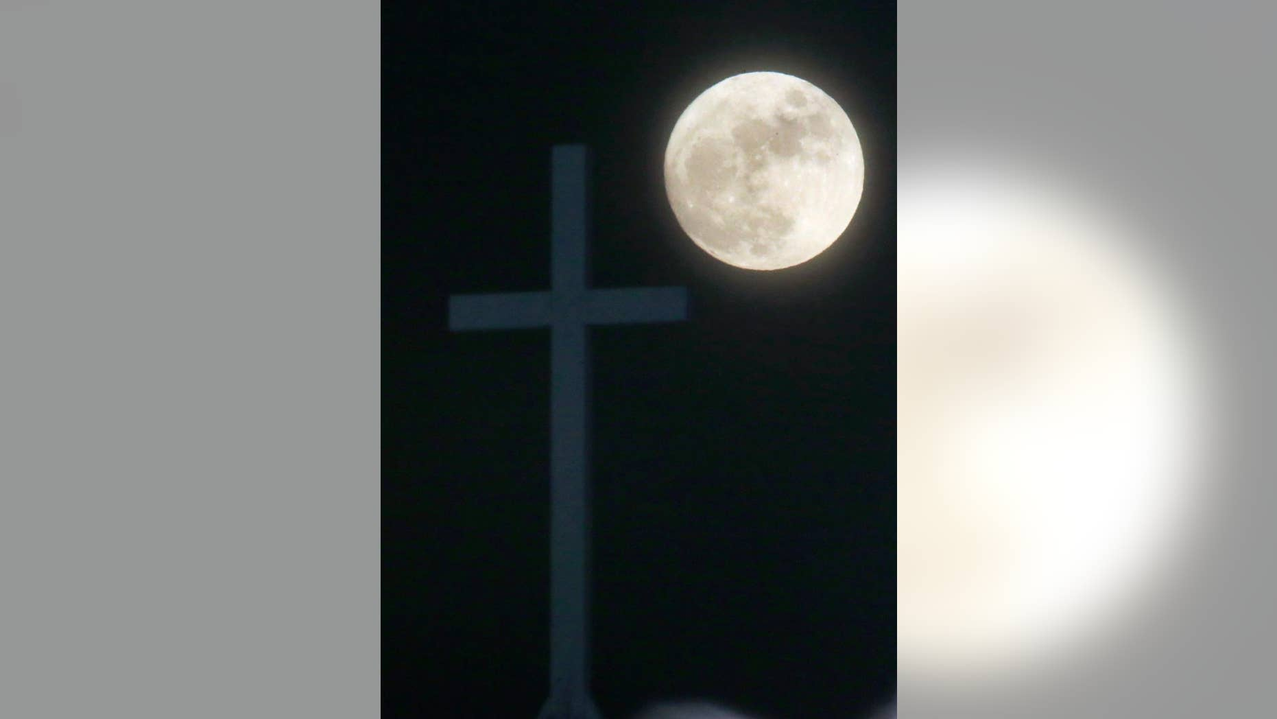 The Long Night Moon rises behind a cross at Christ Community Church in Lawrence, Kan., Thursday, Dec. 24, 2015. When the moon turns full, at 5:11am cst., it will be the first full moon to fall on Christmas day since 1977. Named the Long Night Moon because it's the first full moon to follow the winter solstice, it's also known as the Cold Moon. (AP Photo/Orlin Wagner)