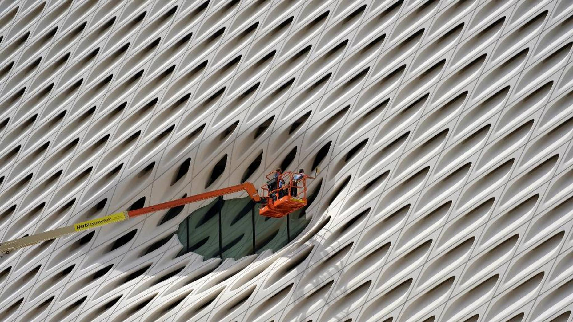 FILE - In this Sept. 1, 2015 file photo, workers clean the facade around a window of the new Broad Museum in downtown Los Angeles. The Conference Board releases its index of leading indicators for August on Friday, Sept. 18, 2015. (AP Photo/Richard Vogel, File)