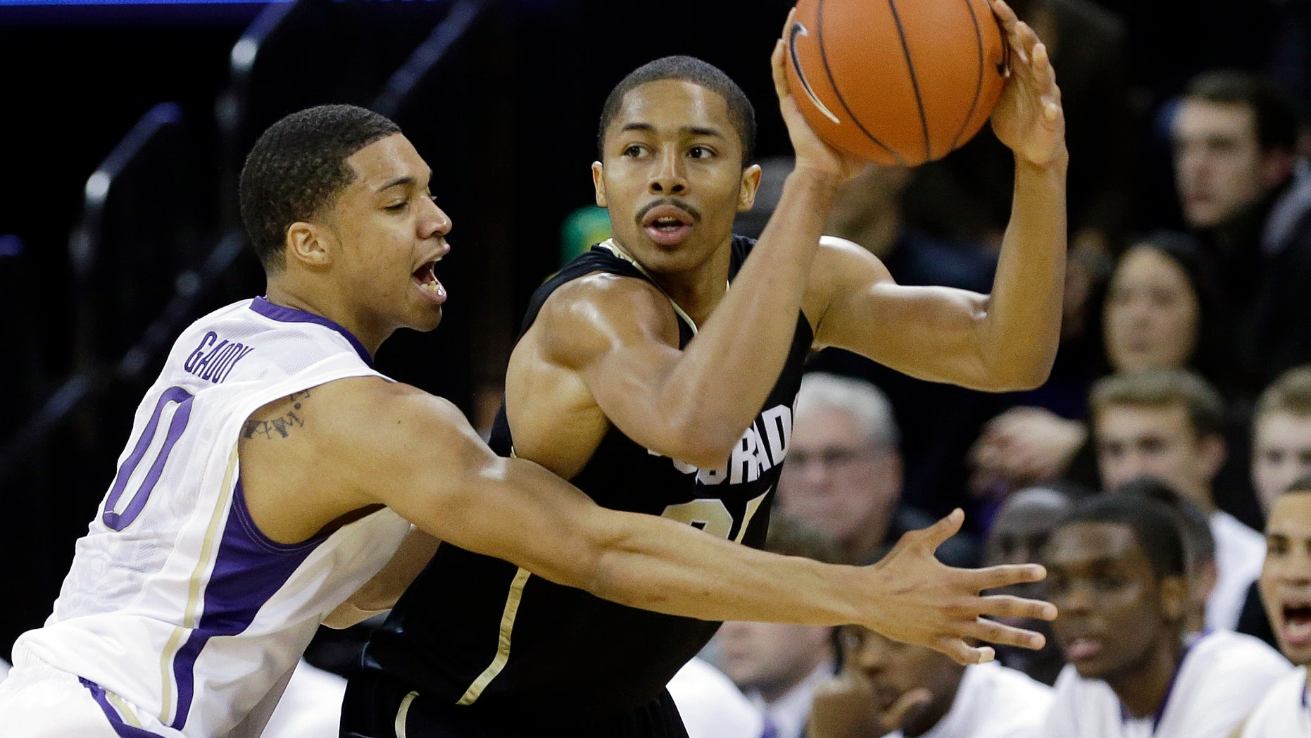 Colorado's Spencer Dinwiddie, right, is defended by Washington's Abdul Gaddy in the first half of an NCAA college basketball game Wednesday, Jan. 16, 2013, in Seattle. (AP Photo/Elaine Thompson)