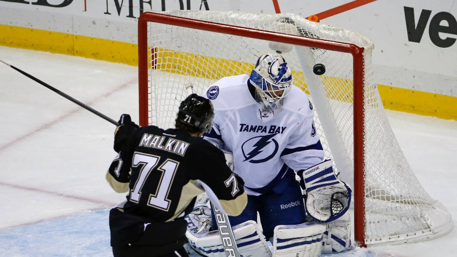 Pittsburgh Penguins' Evgeni Malkin (71) backhands a shot over Tampa Bay Lightning goalie Anders Lindback (39) for a goal in the third period of an NHL hockey game in Pittsburgh, Saturday, March 22, 2014. The Penguins won 4-3 in overtime. (AP Photo/Gene J. Puskar)