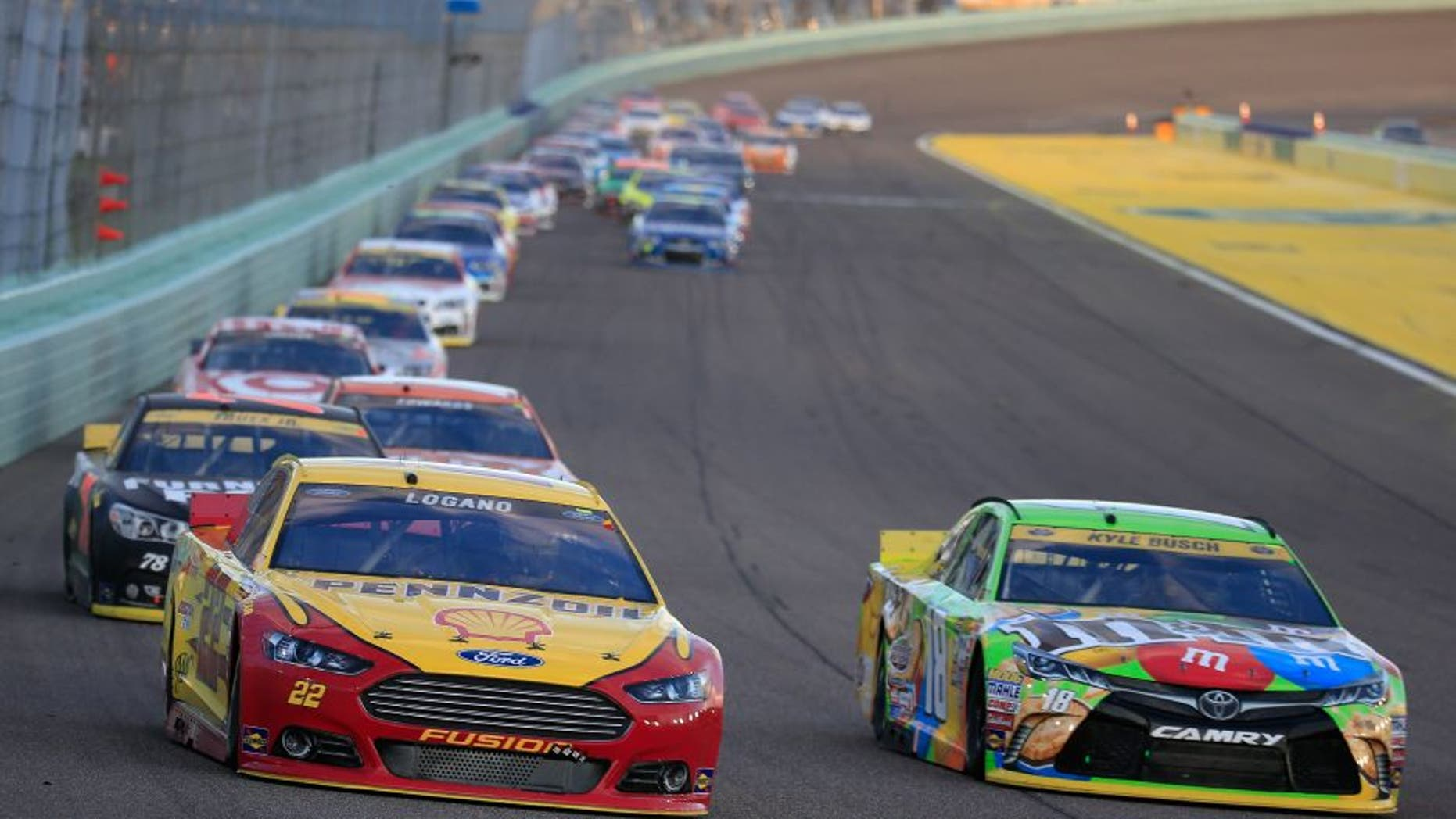HOMESTEAD, FL - NOVEMBER 22: Joey Logano, driver of the #22 Shell Pennzoil Ford, and Kyle Busch, driver of the #18 M&M's Crispy Toyota, race during the NASCAR Sprint Cup Series Ford EcoBoost 400 at Homestead-Miami Speedway on November 22, 2015 in Homestead, Florida. (Photo by Chris Trotman/NASCAR via Getty Images)