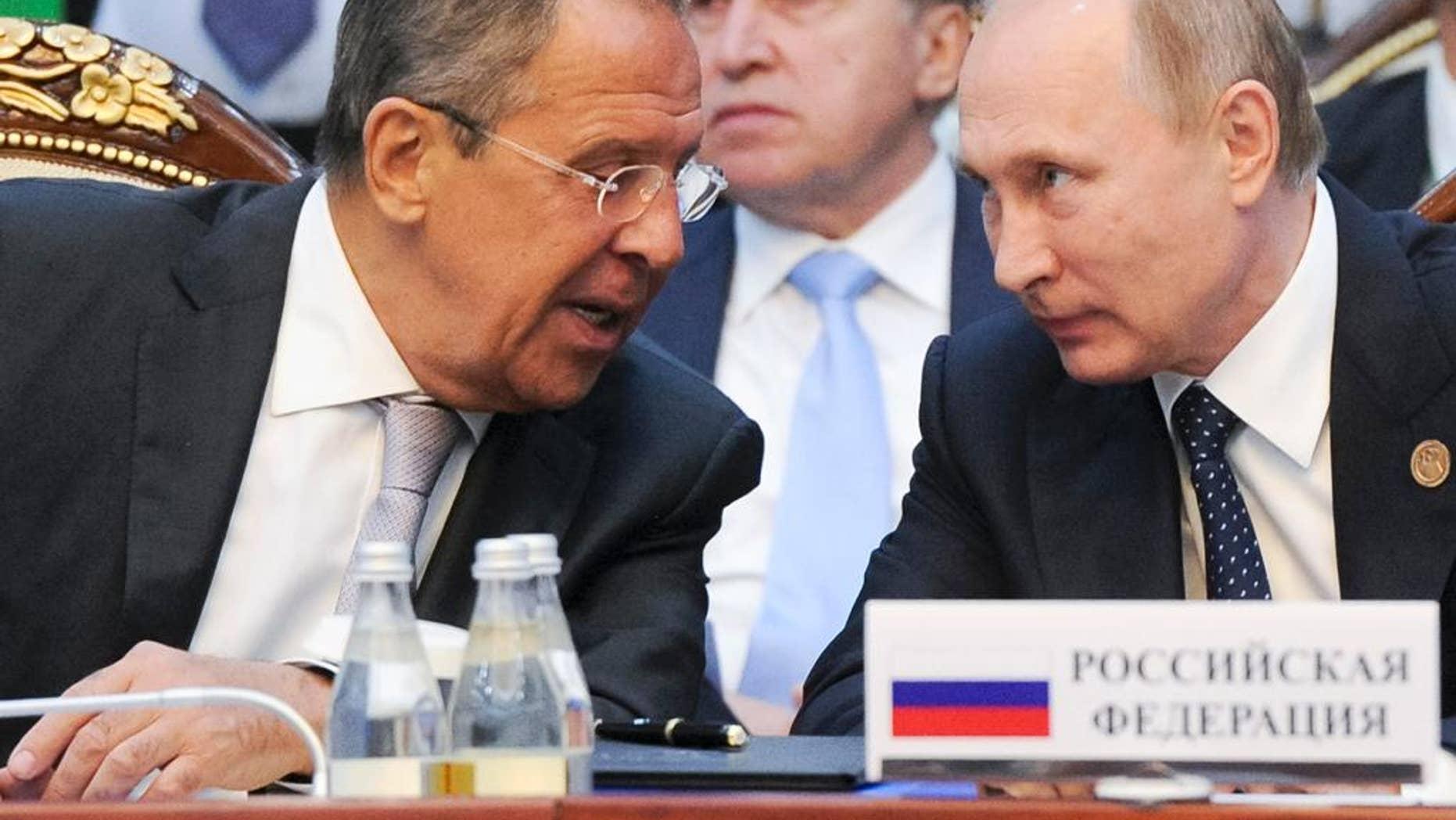 Russian President Vladimir Putin, right, and Russian Foreign Minister Sergey Lavrov speak each other at a CIS (Commonwealth of Independent States, former Soviet republics) summit in Bishkek, Kyrgyzstan, Saturday, Sept. 17, 2016. (Mikhail Klimentyev/Sputnik, Kremlin Pool Photo via AP)