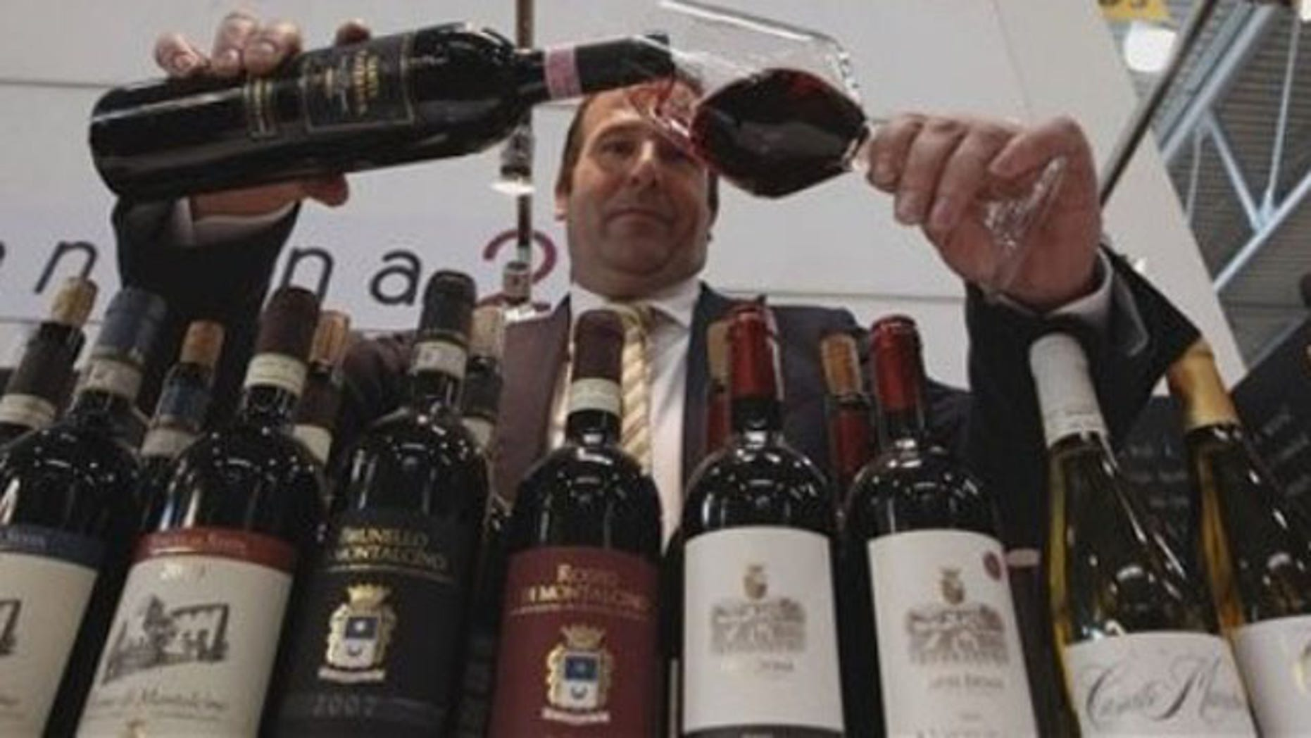 """A man pours a glass of Tuscany red wine during the 46th edition of the annual International Wine and Spirits Exhibition """"Vinitaly"""", in Verona, northern Italy, Monday, March 26, 2012. The wine exhibition runs until March 28.  (AP Photo/Luca Bruno)"""