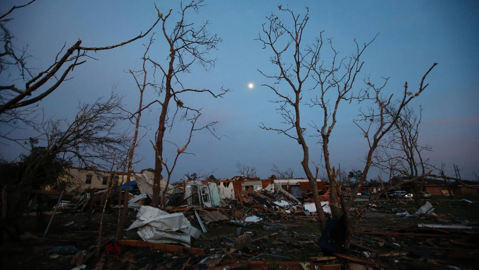 FILE - In this Feb. 8, 2017 file photo, the moon rises over a destroyed neighborhood in the aftermath of a tornado that tore through the New Orleans East section of New Orleans.  Forecasters are warning of severe storms as a powerful system moves across the central United States, the start of what could a turbulent stretch of spring weather over the next few days. The bull's-eye for some of the most fearsome weather _ including possible tornadoes, s over parts of Louisiana, Arkansas and east Texas on Friday, March 24 forecasters said. (AP Photo/Gerald Herbert)