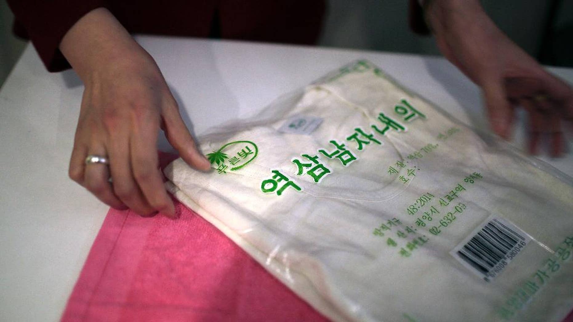 A saleswoman shows off a locally produced t-shirt and towel made out of hemp in Pyongyang. Hemp is, in fact, grown in North Korea with official sanction.
