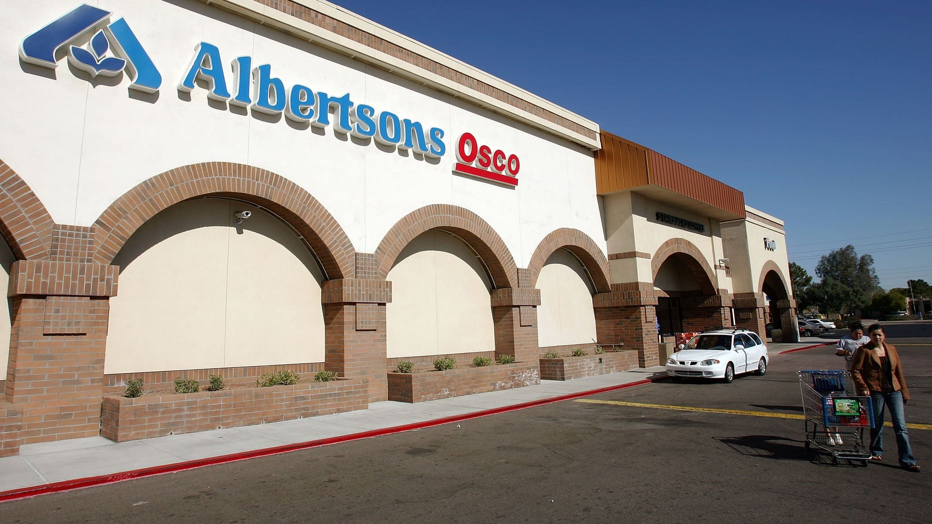 TEMPE, AZ - JANUARY 23:  A customer leaves an Albertsons store January 23, 2006 in Tempe, Arizona. An investment group that includes grocery store operator Supervalu Inc. and the drugstore chain CVS Corp. announced Monday it would buy Albertsons for $17.4 billion in cash, stock and debt.  (Photo by Ethan Miller/Getty Images)