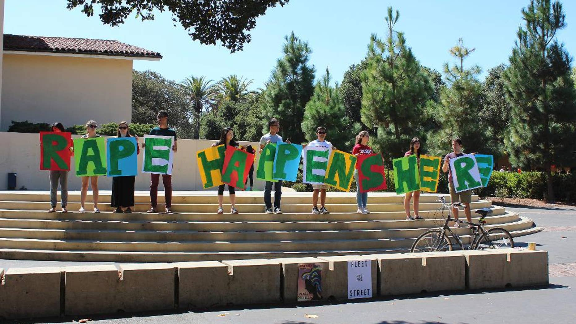 In this Sept. 16, 2015 photo provided by Tessa Ormenyi, students hold up a sign about rape at White Plaza during New Student Orientation on the Stanford University campus in Stanford, Calif. Stanford University considers itself a national leader on preventing and handling sexual assaults, but students have complained that the school isn't doing enough and have drawn attention to the issue by holding demonstrations. (Tessa Ormenyi via AP) MANDATORY CREDIT
