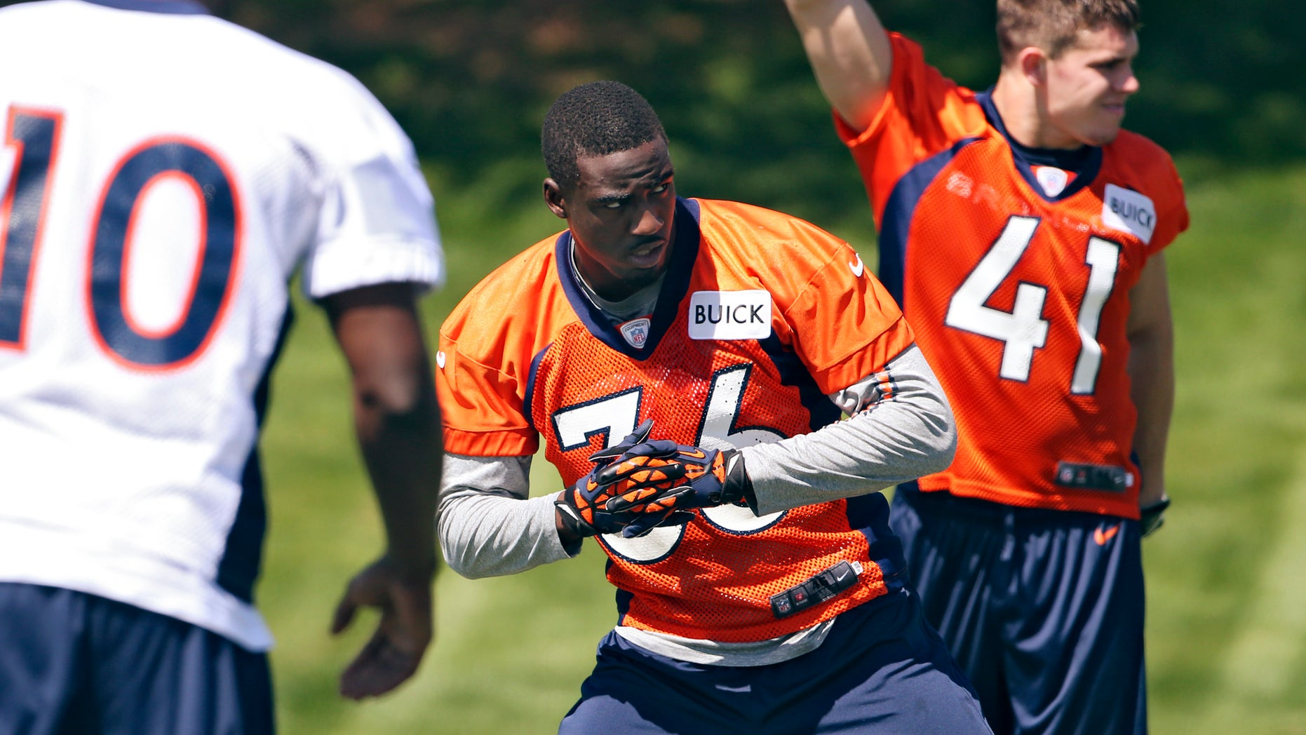 Denver Broncos cornerback Kayvon Webster (36) stretches with teammates Gerell Robinson (10) and Ross Rasner (41) during NFL football rookie minicamp at the team's training facility in Englewood, Colo., Saturday, May 11, 2013. (AP Photo/Ed Andrieski)