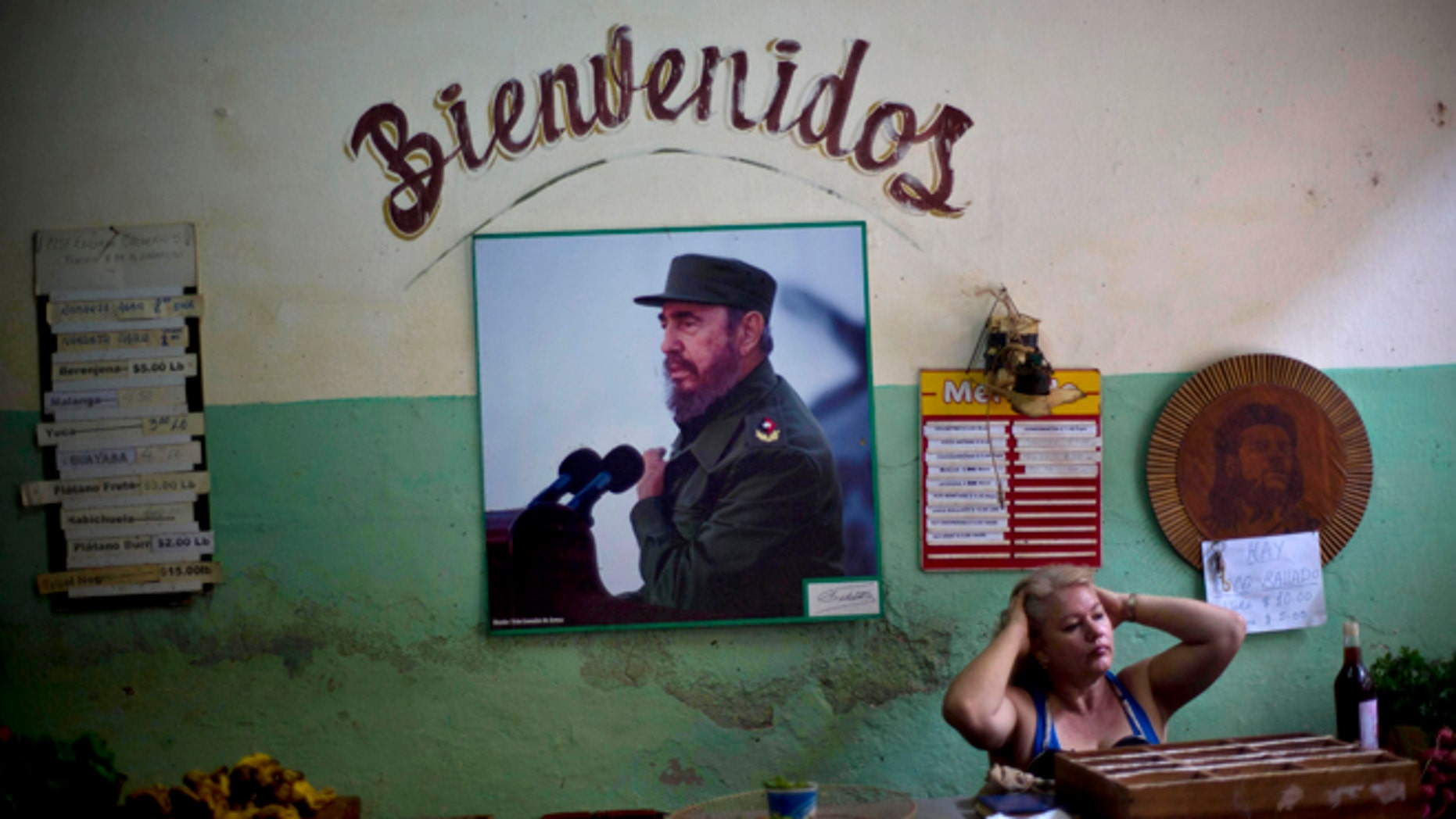 "FILE - In this Dec. 26, 2014 file photo, a photograph of Fidel Castro hangs under the Spanish word ""Welcome"" on the wall at a state-run food market in Havana, Cuba. On Monday, Jan. 26, 2015, after more than a month of silence, Castro made his first public comments about the news that the U.S. and his island nation will restore diplomatic relations after more than 50 years of hostility. (AP Photo/Ramon Espinosa, File)"