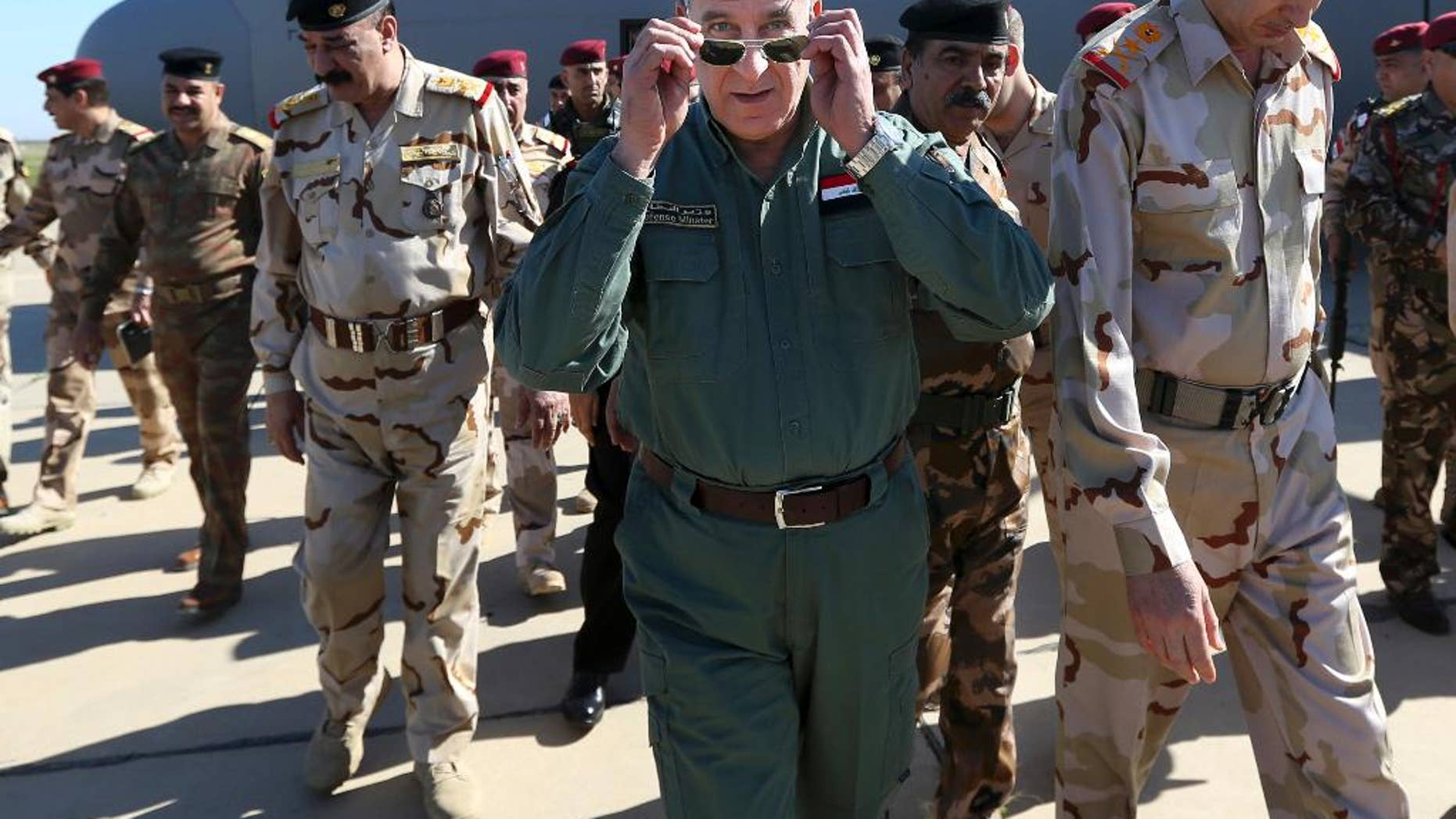 FILE - In this Wednesday, March 9, 2016 file photo, Iraqi Defense Minister Khaled al-Obeidi, center, arrives at a military a base outside Tikrit, 130 kilometers (80 miles) north of Baghdad, Iraq. Al-Obeidi has received a no-confidence vote from parliament just as Iraqi forces retook a key northern town near the Islamic State-held city of Mosul on Thursday, Aug. 25, 2016. He is the first sitting defense minister to receive a no confidence vote from parliament since the overthrow of former Iraqi leader Saddam Hussein in 2003.  (AP Photo/Hadi Mizban, File)