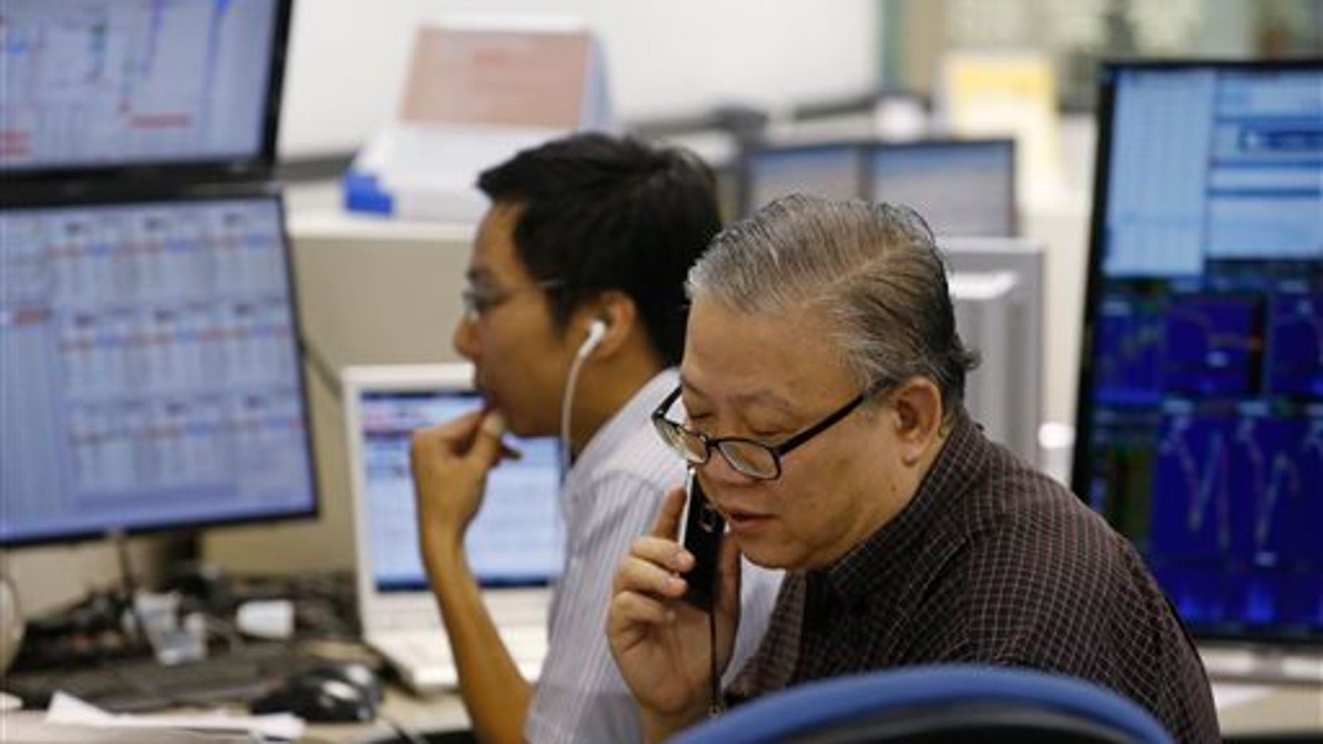 A broker talks on phone at a brokerage firm in Hong Kong, Wednesday, July 8, 2015.