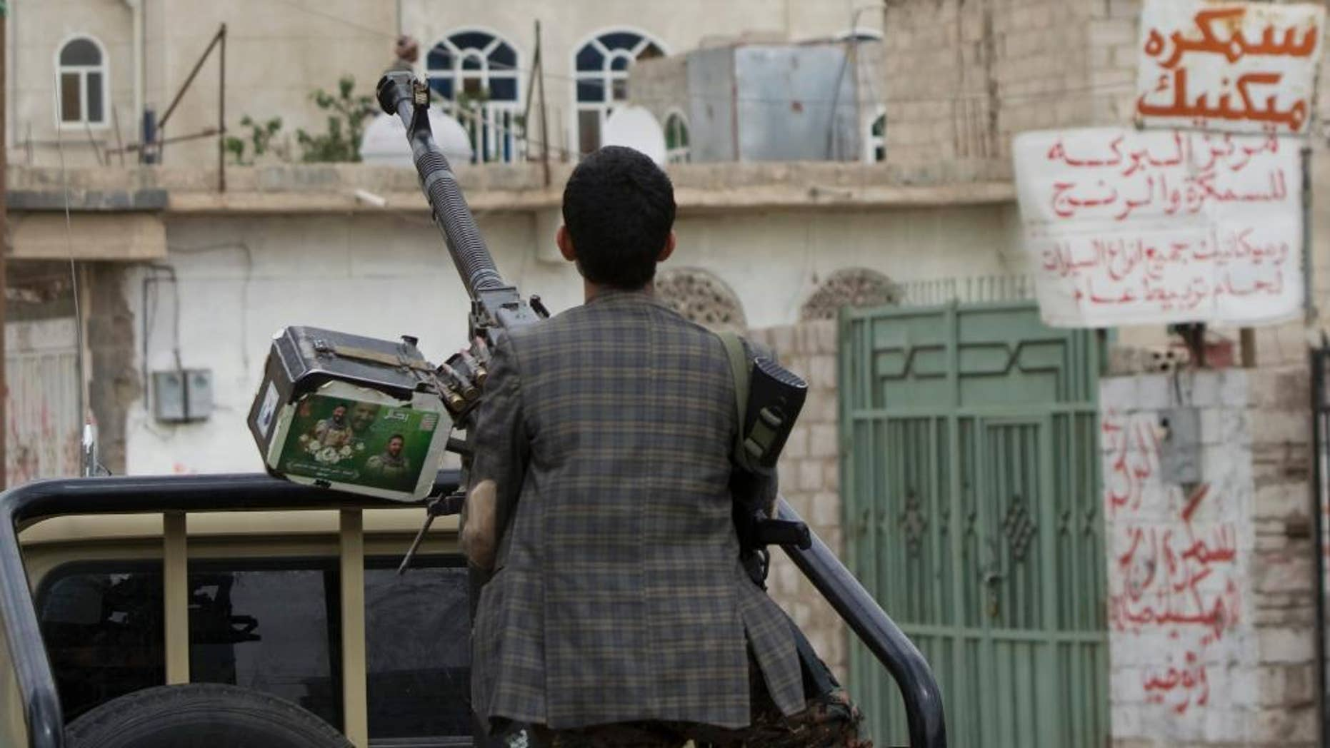 A Shiite fighter known as a Houthi holds a weapon as he looks at smoke rising from a building after a Saudi-led airstrike on a street in Sanaa, Yemen, Wednesday, April 8, 2015. Iran dispatched a naval destroyer and another vessel Wednesday to waters near Yemen as the United States quickened weapons supply to the Saudi-led coalition striking rebels there, underlining how foreign powers are deepening their involvement in the conflict. (AP Photo/Hani Mohammed)