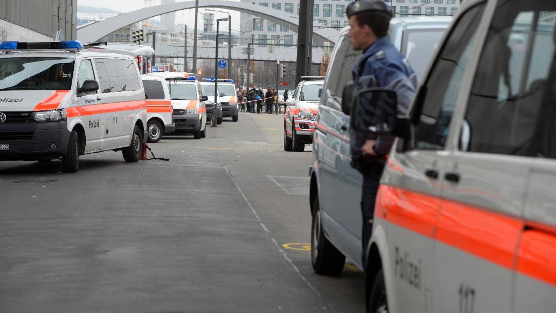 Police cars wait outside the Zurich, Switzerland, university of art Thursday morning Dec. 4, 2014 after an alarm was given. Police wasn't able to immediately give the reason for the alarm.  (AP Photo/Keystone, Walter Bieri)