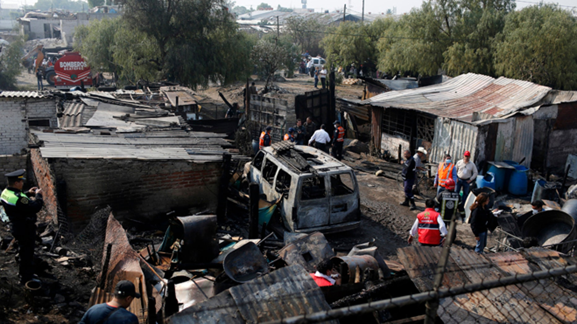May 7, 2013: Police officers and rescue workers stand at an area damaged by the explosion of a gas tanker truck in San Pedro Xalostoc, on the outskirts of Mexico City.