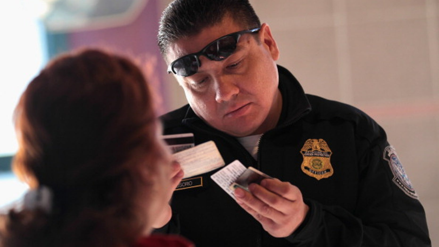 """NOGALES, AZ - DECEMBER 10:  Officer Juan Osorio inspects the identifications of a Mexican citizen at the U.S.-Mexico border crossing on December 10, 2010 in Nogales, Arizona. Despite Arizona's tough immigration enforcement laws, thousands of Mexican citizens have permits to work in the U.S. and commute daily from their homes across the border in Mexico. Border crossings, known as """"ports of entry,"""" are run by the U.S. Office of Field Operations, which is part of the department of U.S. Customs and Border Protection. Port personnel are the face at the border for most visitors and cargo entering the United States and are authorized to stop, question, search and examine everyone entering the country.  (Photo by John Moore/Getty Images)"""