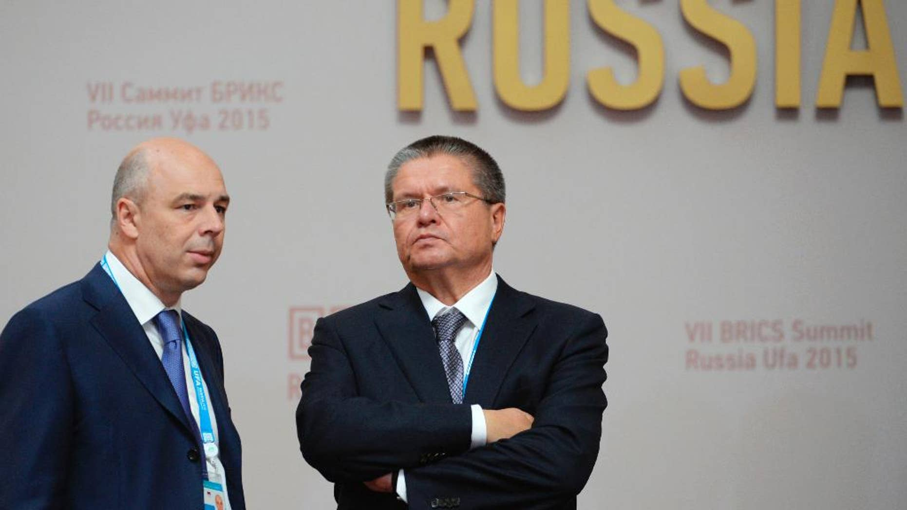 FILE - In this file photo taken on Thursday, July 9, 2015, Anton Siluanov, left, Minister of Finance of the Russian Federation, and Alexey Ulyukayev, Minister of Economic Development of the Russian Federation speak in Ufa, Russia. A long-serving Russian minister has been detained over an alleged $2 million bribe, the most senior government official to face corruption charges in a quarter-century. (Government Pool Photo via AP, File)