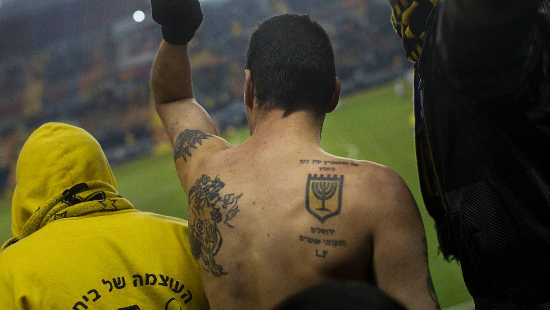 """In this Tuesday, Jan. 29, 2013 file photo, Beitar Jerusalem F.C. soccer supporters watch a State Cup soccer match against Maccabi Umm al-Fahm F.C. at the Teddy Stadium in Jerusalem. Israeli police say they have arrested dozens of members of an extremist soccer fans' group. Police spokeswoman Luba Samri said on Tuesday, July 26, 2016 that 56 suspected members of the """"La Familia"""" group of Beitar Jerusalem fans were arrested in an overnight raid. (AP Photo/Bernat Armangue, File)"""