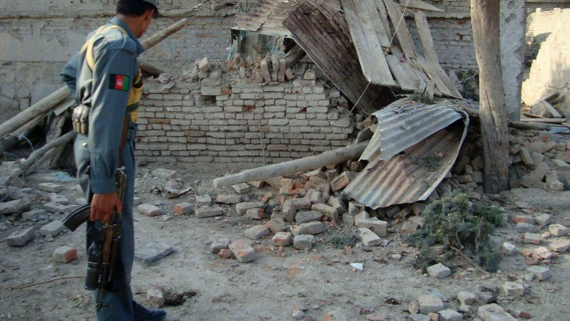 FILE - In this July 25, 2009 file photo, an Afghan police officer looks at a guard post which was damaged in an attack in Khost, east of Kabul, Afghanistan. Recently declassified U.S. government cables suggest Pakistan's intelligence service paid a U.S.-designated terrorist organization $200,000 to carry out one of the deadliest attacks against the CIA in the spy agency's history. But a U.S. intelligence official said the information was uncorroborated and inconsistent with what is known about the 2009 suicide bombing at Camp Chapman in Khost, Afghanistan, near the Pakistani border. (AP Photo/Nishanuddin Khan, File)