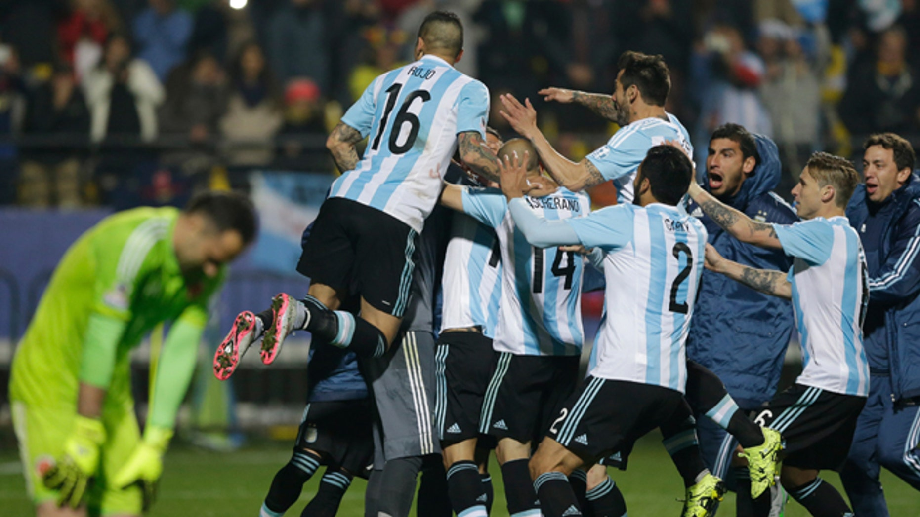 Argentina's players jump over Carlos Tevez after scored the winning penalty kick against Colombia during a Copa America quarterfinal soccer match at the Sausalito Stadium in Vina del Mar, Chile, Friday, June 26, 2015. (AP Photo/Ricardo Mazalan)