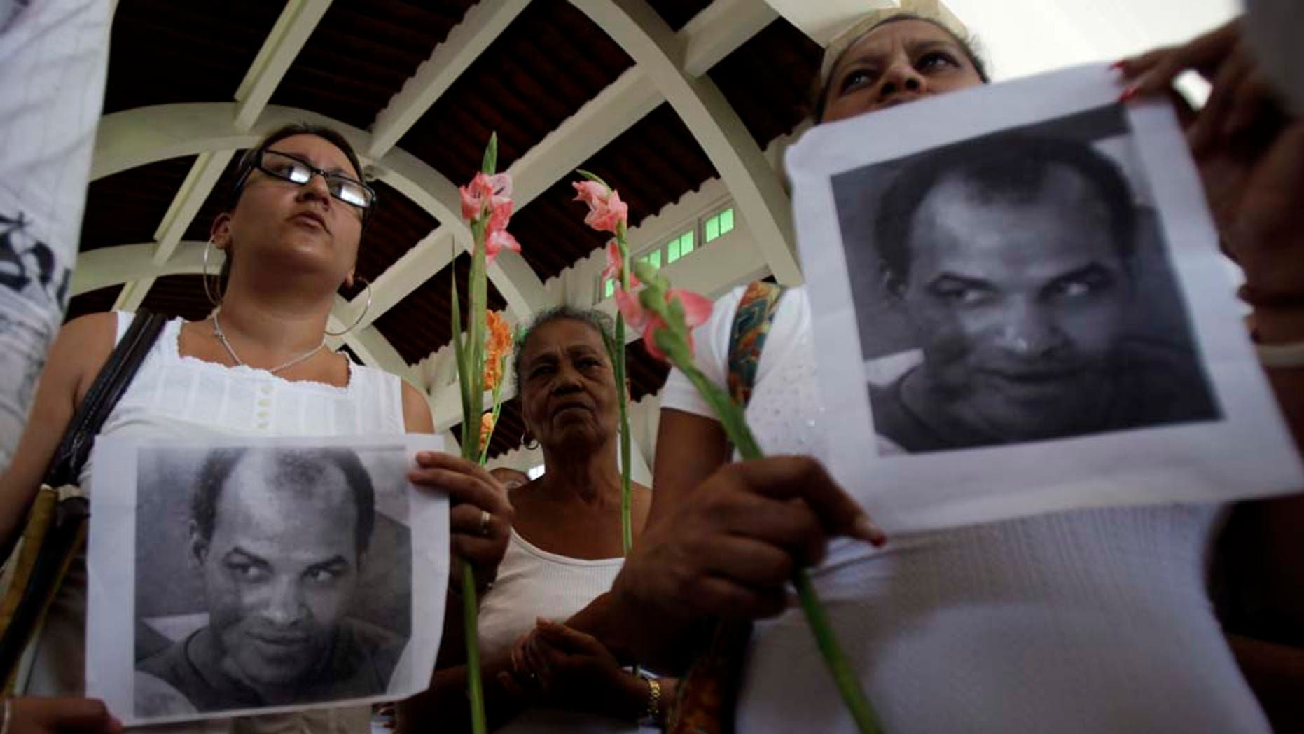 Members of Cuba's dissident group Ladies in White hold up photographs of the late political prisoner Orlando Zapata Tamayo during their weekly march in Havana, Cuba, Sunday, Feb. 6, 2011. Tamayo died on Feb. 23 following a lengthy hunger strike. Cuba freed Guido Sigler , a prominent political prisoner, on Friday and the Roman Catholic Church said Angel Moya, another political prisoner, would be released soon and allowed to stay in the country. (AP Photo/Javier Galeano)