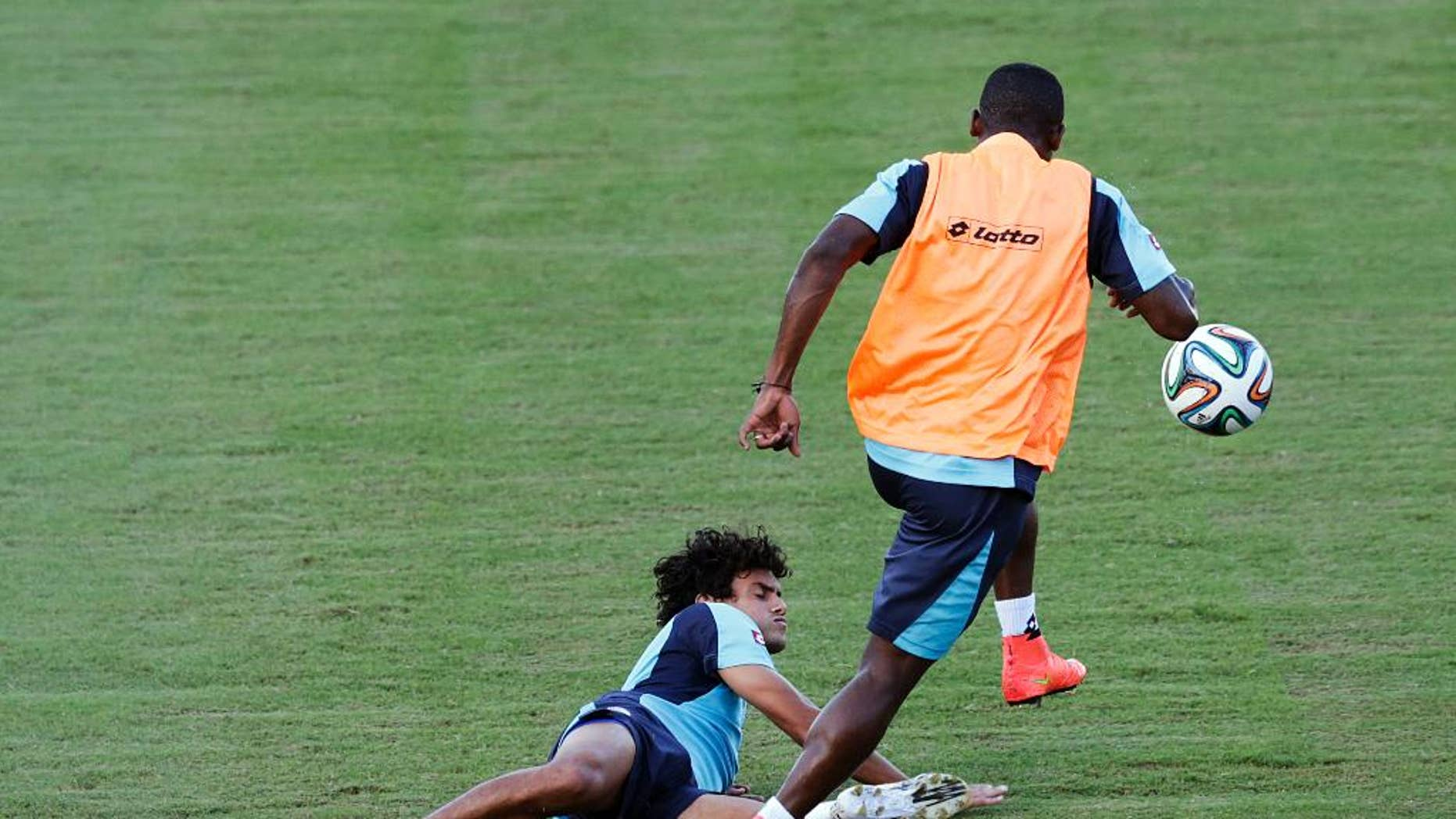 Costa Rica's Yeltsin Tejeda falls as he is tackled during a training session in Salvador, Brazil, Friday, July 4, 2014. Costa Rica play their quarterfinal match of the 2014 World Cup soccer tournament against Netherlands on July 5 in Salvador(AP Photo/Wong Maye-E)