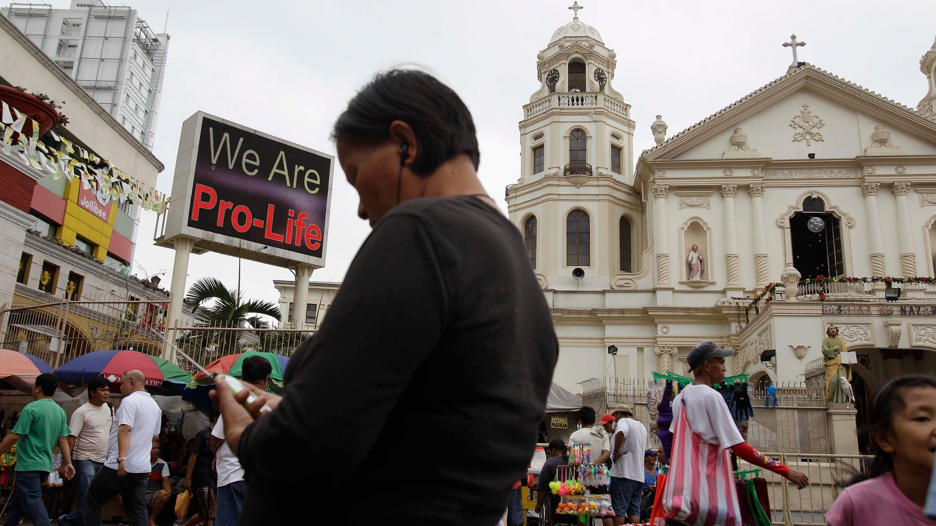 """A """"Pro-Life"""" sign flashes on an electric signboard outside the Roman Catholic Minor Basilica of the Black Nazarene in downtown Manila, Philippines on Thursday, Jan. 3, 2013. Philippine President Benigno Aquino III last month signed the Responsible Parenthood and Reproductive Health Act of 2012. The law that provides state funding for contraceptives for the poor pitted the dominant Roman Catholic Church in an epic battle against the popular Aquino and his followers. (AP Photo/Aaron Favila)"""