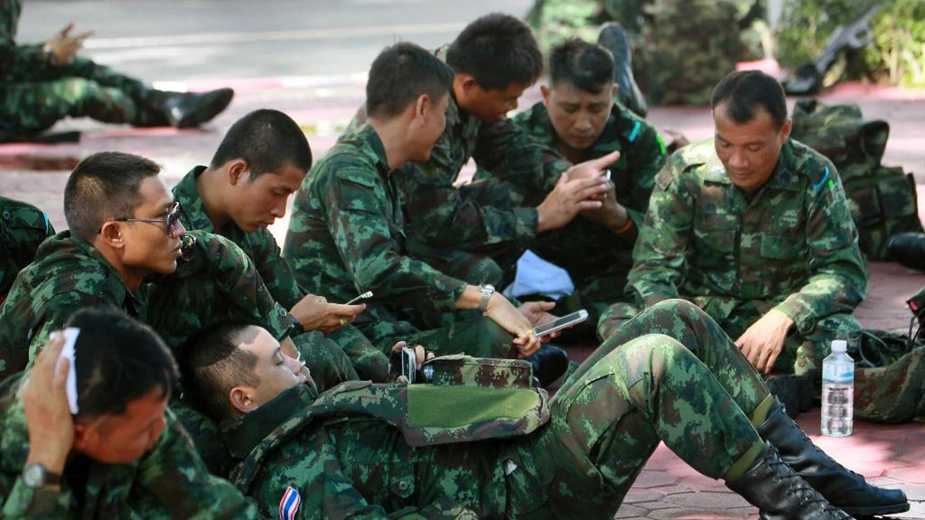 Thai soldiers rest on the ground at police headquarters after being deployed to prevent an anti-coup demonstration in Bangkok, Thailand Sunday, June 1, 2014. An anti-coup activist in Thailand called Friday for a weekend rally to defy the military government's ban on demonstrations, urging those opposed to the takeover to wear masks and be ready for cat-and-mouse chases with soldiers in the capital. (AP Photo/Wason Wanichakorn)