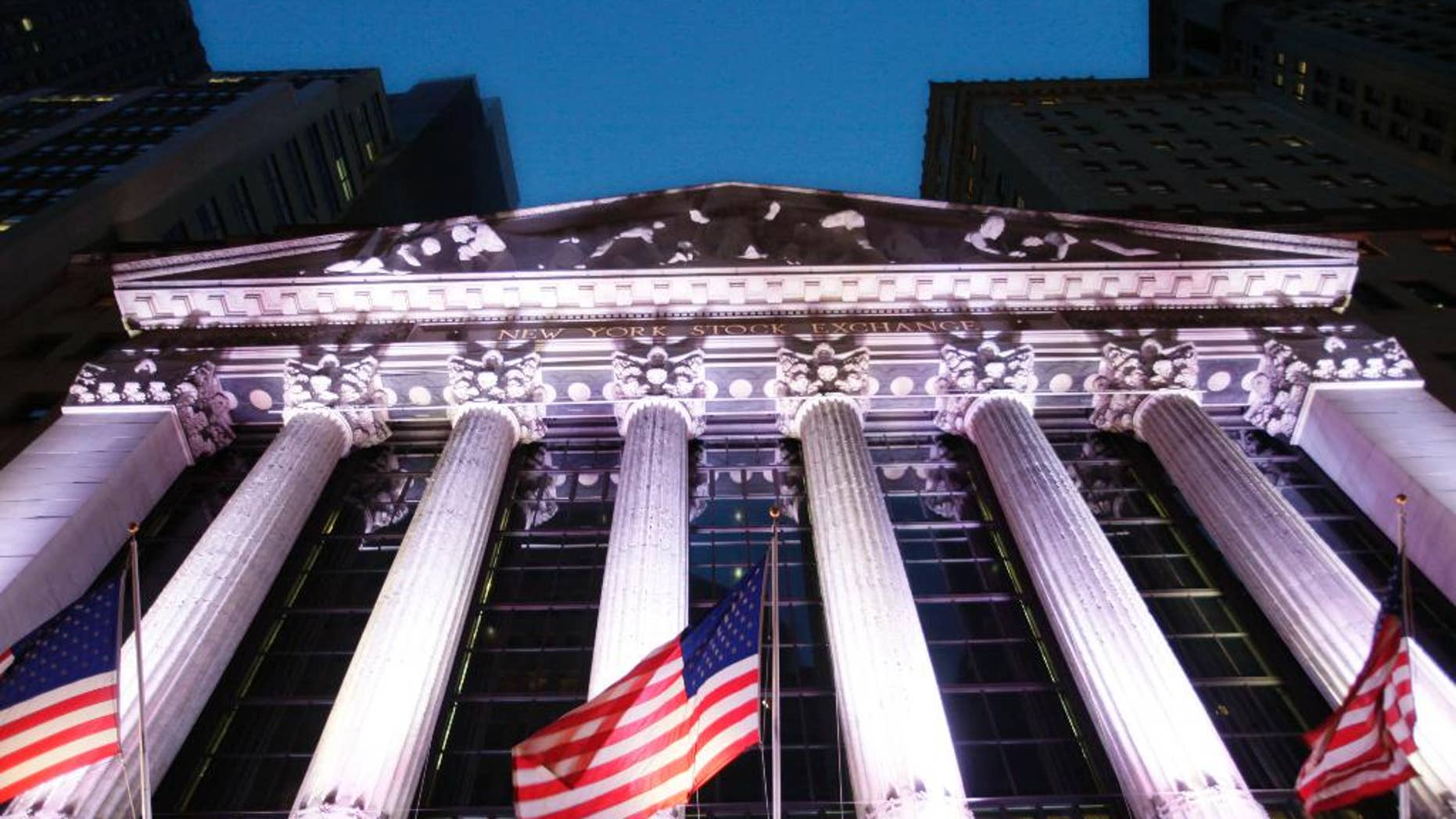 In this Wednesday, Oct. 8, 2014 photo, American flags fly in front of the New York Stock Exchange, in New York. A strong report on job creation pushed stock indexes higher Friday, Dec. 5, 2014, even though the figures may prompt the Federal Reserve to raise interest rates sooner than anticipated. The dollar rose as traders anticipated more robust growth in the U.S. (AP Photo/Mark Lennihan)