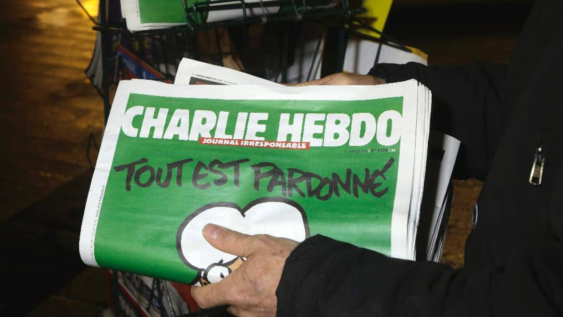 FILE - In this Wednesday, Jan. 14, 2015, file photo, a seller of newspapers stocks several Charlie Hebdo newspapers at a newsstand in Nice, France. The French satirical newspaper Charlie Hebdo will publish a German version in the country that has given the best reception to the weekly paper outside France since the attacks that wiped out the Paris editorial staff in January 2015. (AP Photo/ Lionel Cironneau, File)