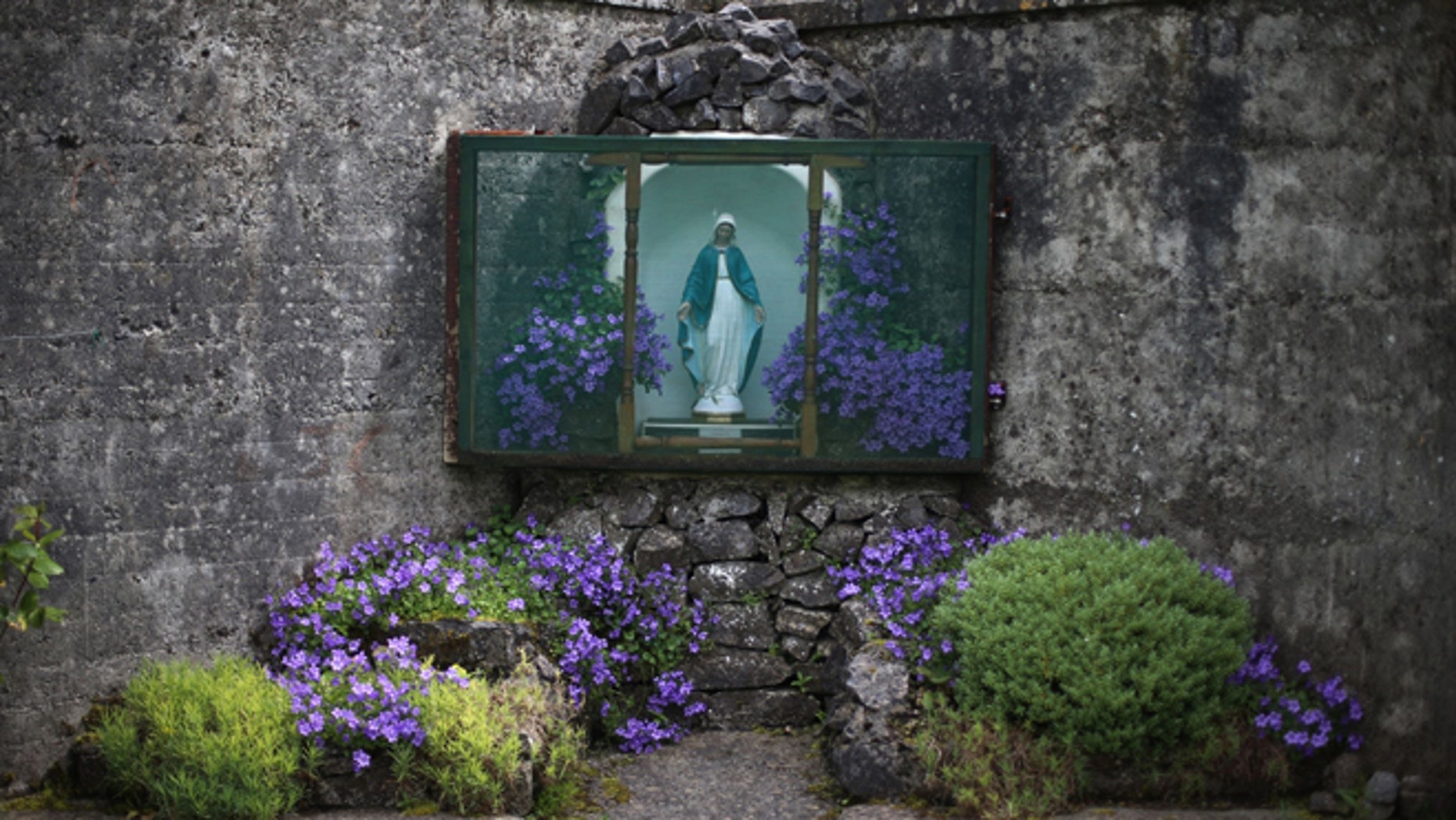 June 4, 2014: A statue of the Virgin Mary adorns the site of a mass grave for children who died in the Tuam mother and baby home in Tuam, Ireland. (AP/Niall Carson/PA)