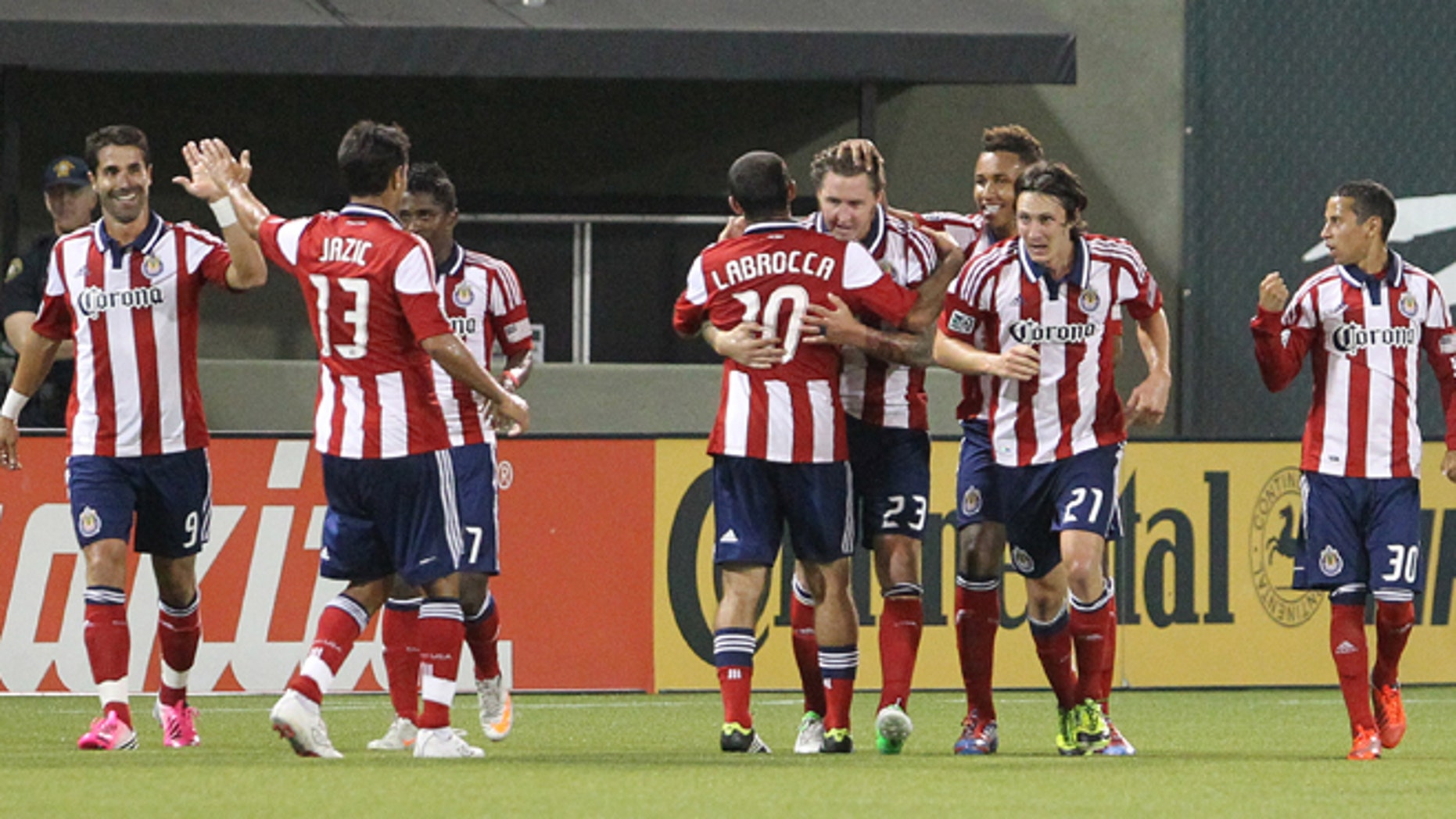 FILE - This July 28, 2012, file photo shows Chivas USA's Danny Califf (23) embraces teammate Nick LaBrocca (10) after he scores in the second half during an MLS soccer game with the Portland Timbers in Portland, Ore. Chivas USA ceased operations on Monday, Oct. 27, 2014, after 10 troubled and unsuccessful years in Major League Soccer, with the league planning a new franchise for Los Angeles that will begin play in 2017 with new ownership and a new soccer-specific stadium. (AP Photo/Rick Bowmer, File)