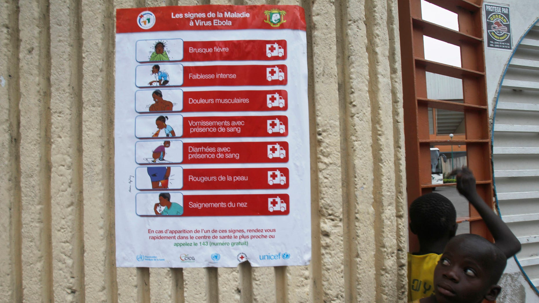 Boys stand next to a poster, pertaining to the Ebola virus, during a training session by Sierra Leone's national soccer team  at the Felix Houphouet Boigny stadium in Abidjan, September 5, 2014. Ivory Coast will host their African Nations Cup qualifier against Ebola-affected Sierra Leone this weekend following a special meeting of the country?s national security council. The decision, announced in a government statement published in local media on Tuesday, comes one week after the government said it would not allow the match to go ahead, citing concerns over a possible Ebola outbreak. REUTERS/Luc Gnago (IVORY COAST - Tags: SPORT SOCCER HEALTH) - RTR4552S