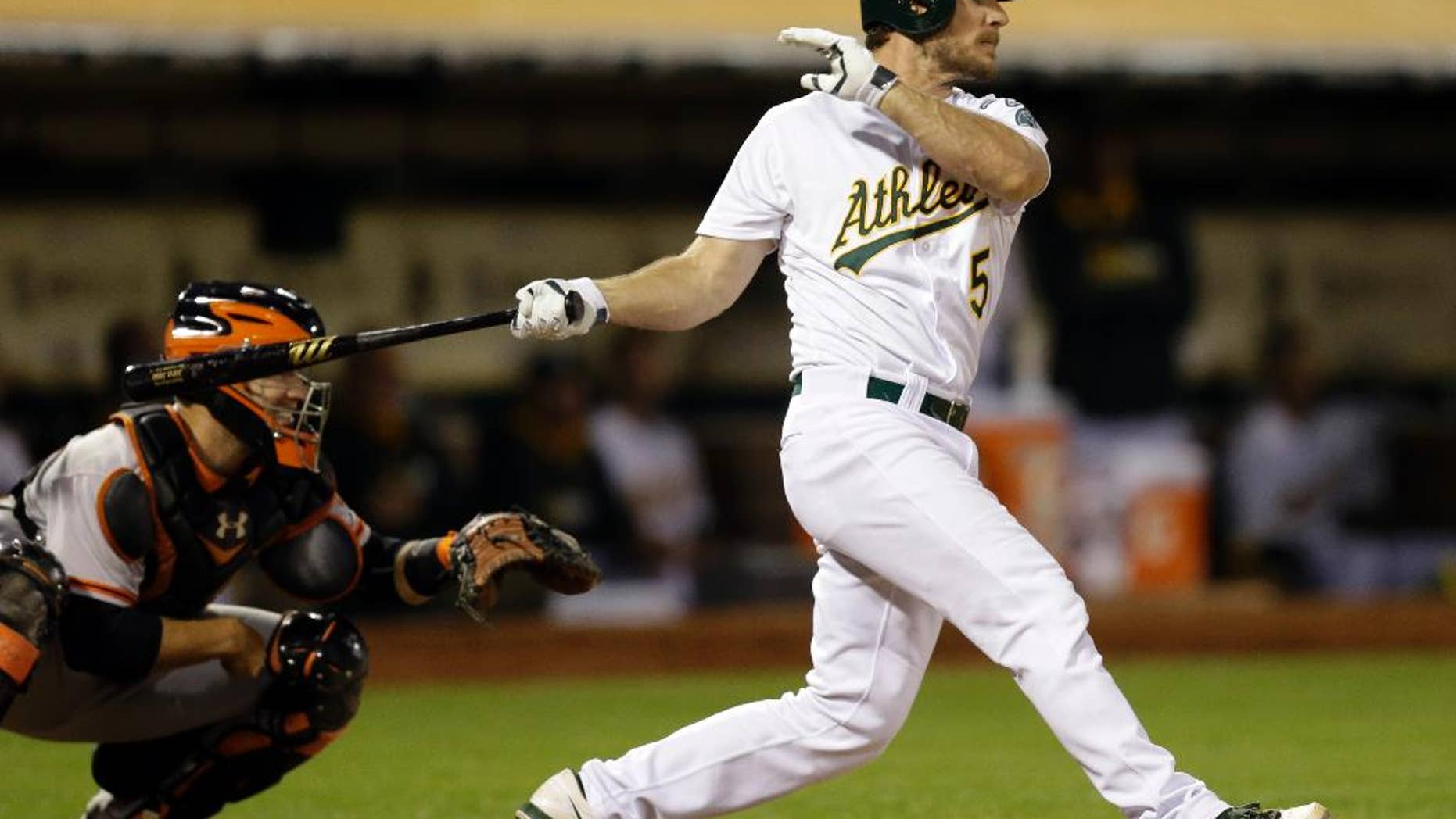 Oakland Athletics' John Jaso swings for an RBI ground out against the San Francisco Giants in the fifth inning of a baseball game Monday, July 7, 2014, in Oakland, Calif. (AP Photo/Ben Margot)