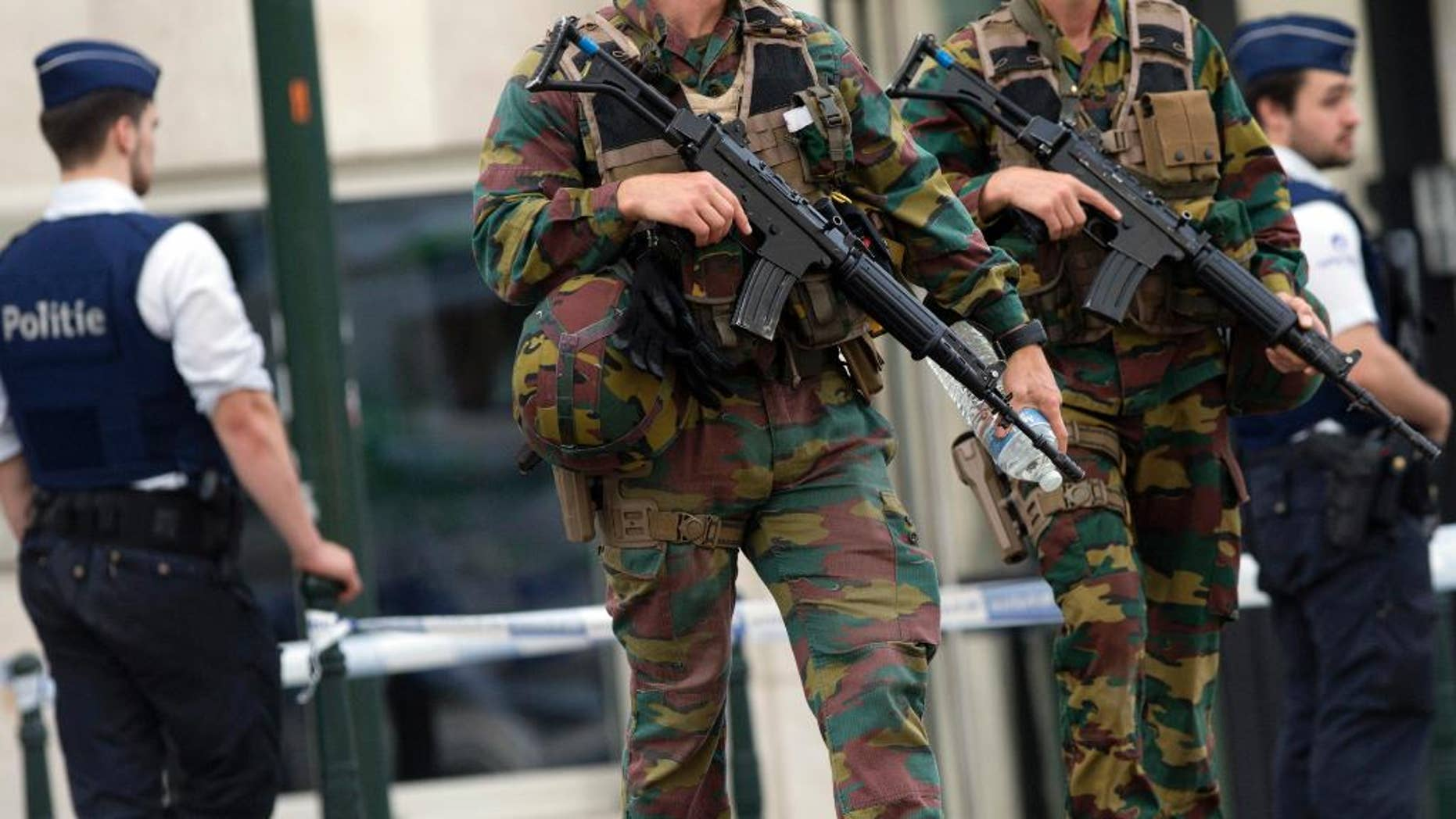 FILE - In this June 23, 2016, file photo, folice and Belgian Army soldiers patrol during a court hearing for suspect Mohamed Abrini, a suspect in the Paris and Brussels attacks, that were claimed by the Islamic State organization, at the Court of Appeals in Brussels. The threat of violence by people inspired by foreign extremists invokes fear in a majority of young Americans across racial groups. But for young people of color, particularly African Americans, that fear is matched or surpassed by worries about violence from white extremists. A new GenForward poll of Americans age 18-30 shows widespread anxiety among young people about attacks from both inside and outside the United States. (AP Photo/Virginia Mayo, File)