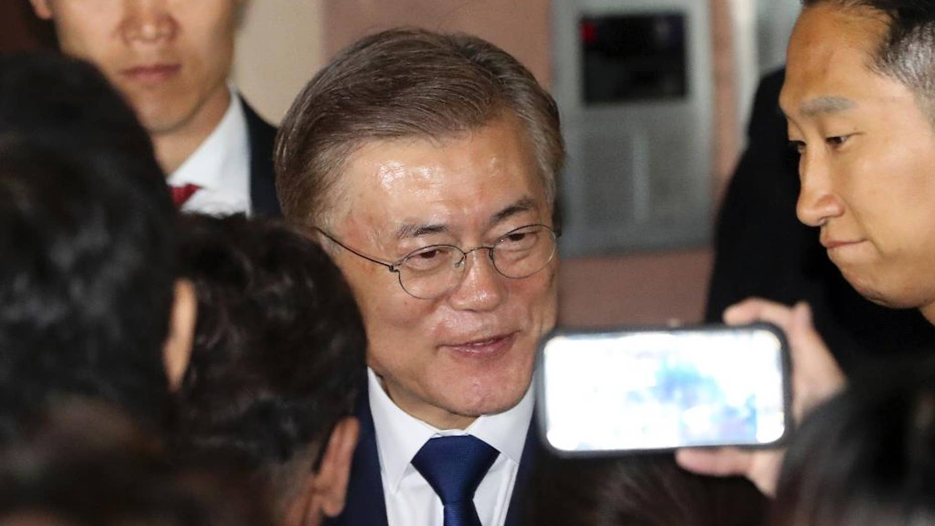 South Korea's presidential candidate Moon Jae-in of the Democratic Party is greeted by supporters in front of his house in Seoul, South Korea, Tuesday, May 9, 2017.   Moon Jae-in declared victory in South Korea's presidential election Tuesday after his two main rivals conceded. (AP Photo/Lee Jin-man)