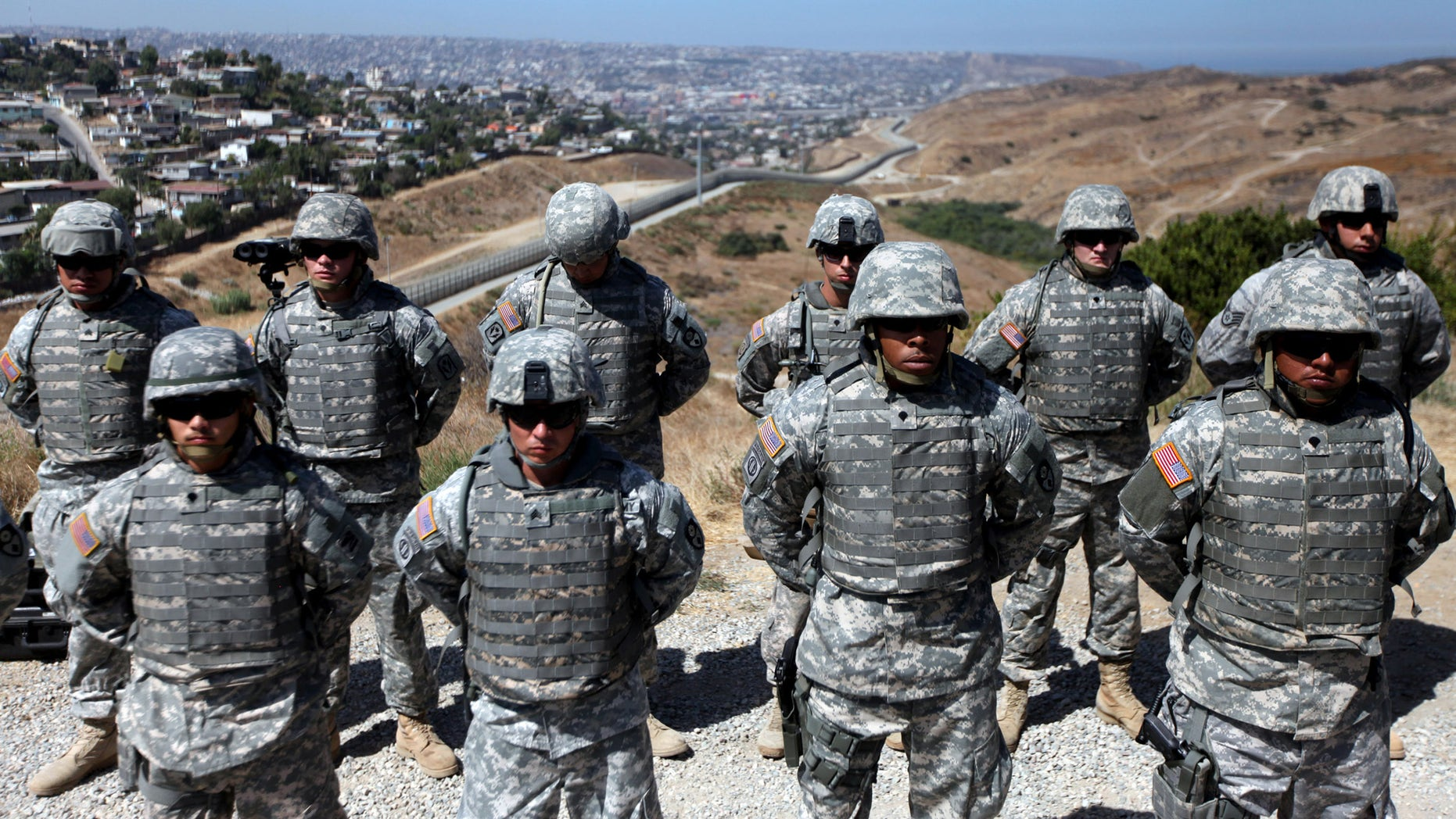 SAN YSIDRO, CA - AUGUST 18:  National Guardsmen stand in formation along the U.S.-Mexico border during a visit by California Gov. Arnold Schwarzenegger August 18, 2010 in San Ysidro, California.  U.S. President Barack Obama has ordered more than a thousand National Guard troops to the border in response to border patrol agents who are overwhelmed by drug smugglers and illegal immigrants.  (Photo by Sandy Huffaker/Getty Images)