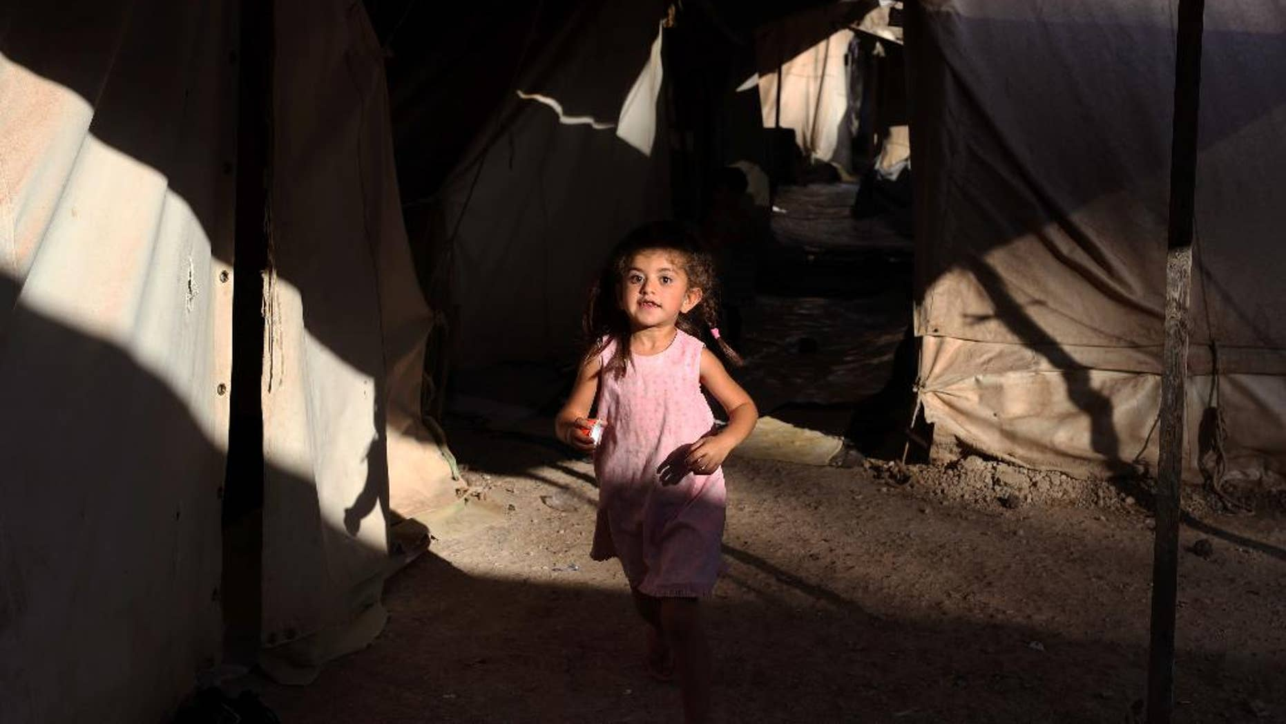 A little girl runs among tents as she plays with other children at Ritsona refugee camp, which hosts about 600 refugees and migrants, north of Athens, Monday, Sept. 12, 2016. The European Union will add 115 million euros ($129 million) in funding to humanitarian organizations in Greece to assist programs for refugees and migrants before the winter, officials said Saturday. (AP Photo/Petros Giannakouris)