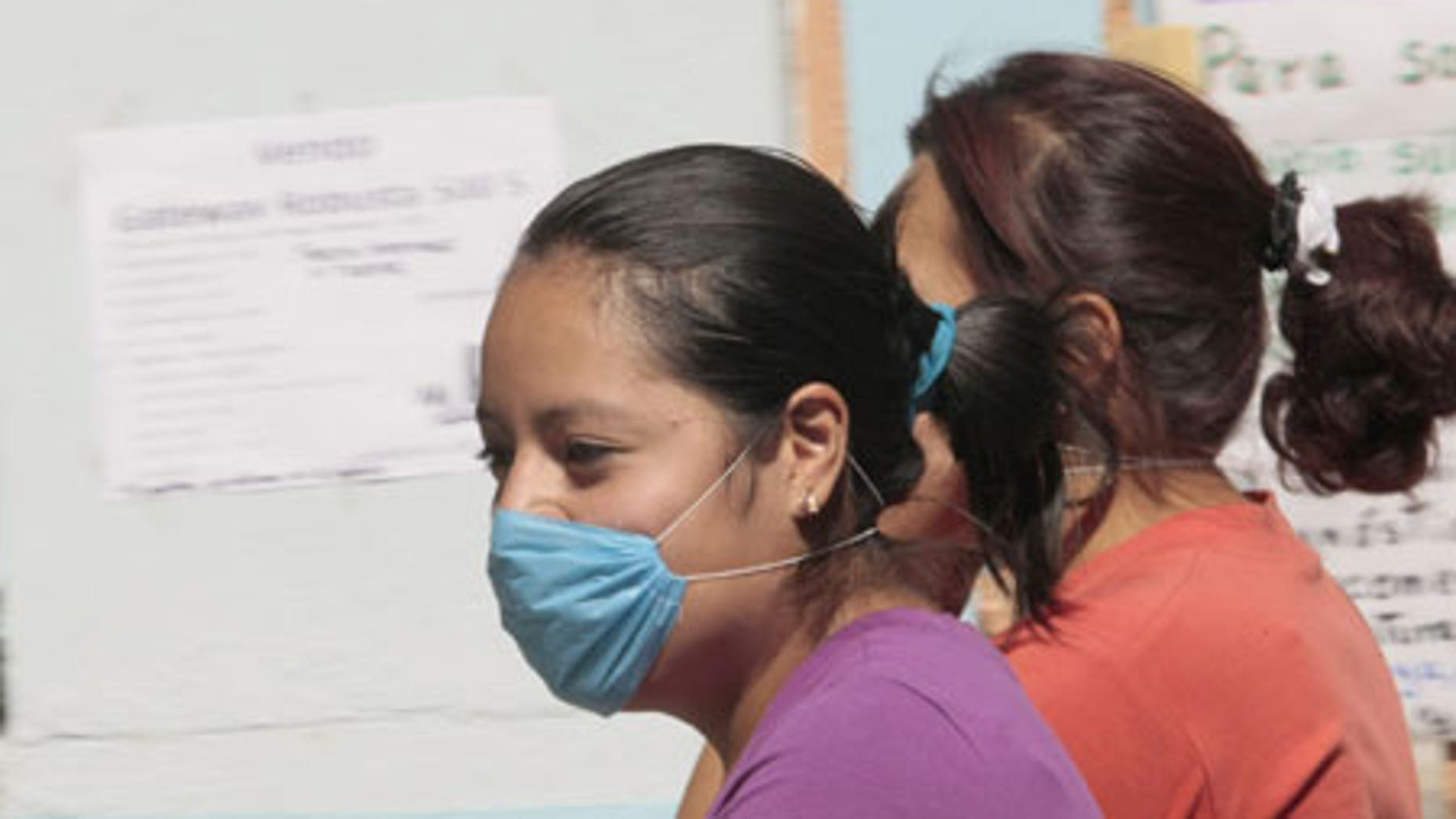 April 24, 2009: Women wear masks as they walk past a closed school in Mexico City.
